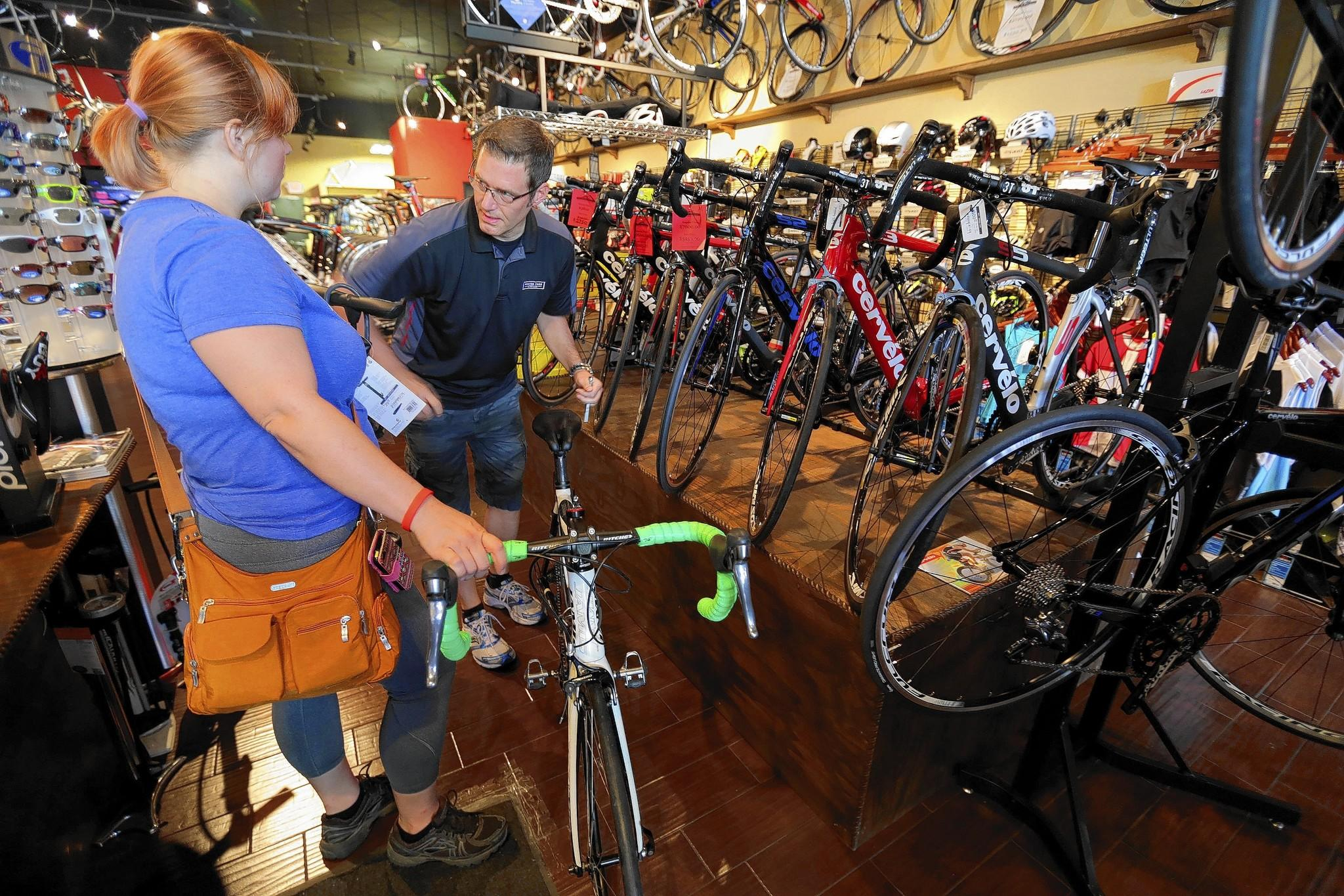 Anne Marie Harpstreit of Lake Mary talks to manager Lee Hamilton at the Winter Park Cycles store in Lake Mary.