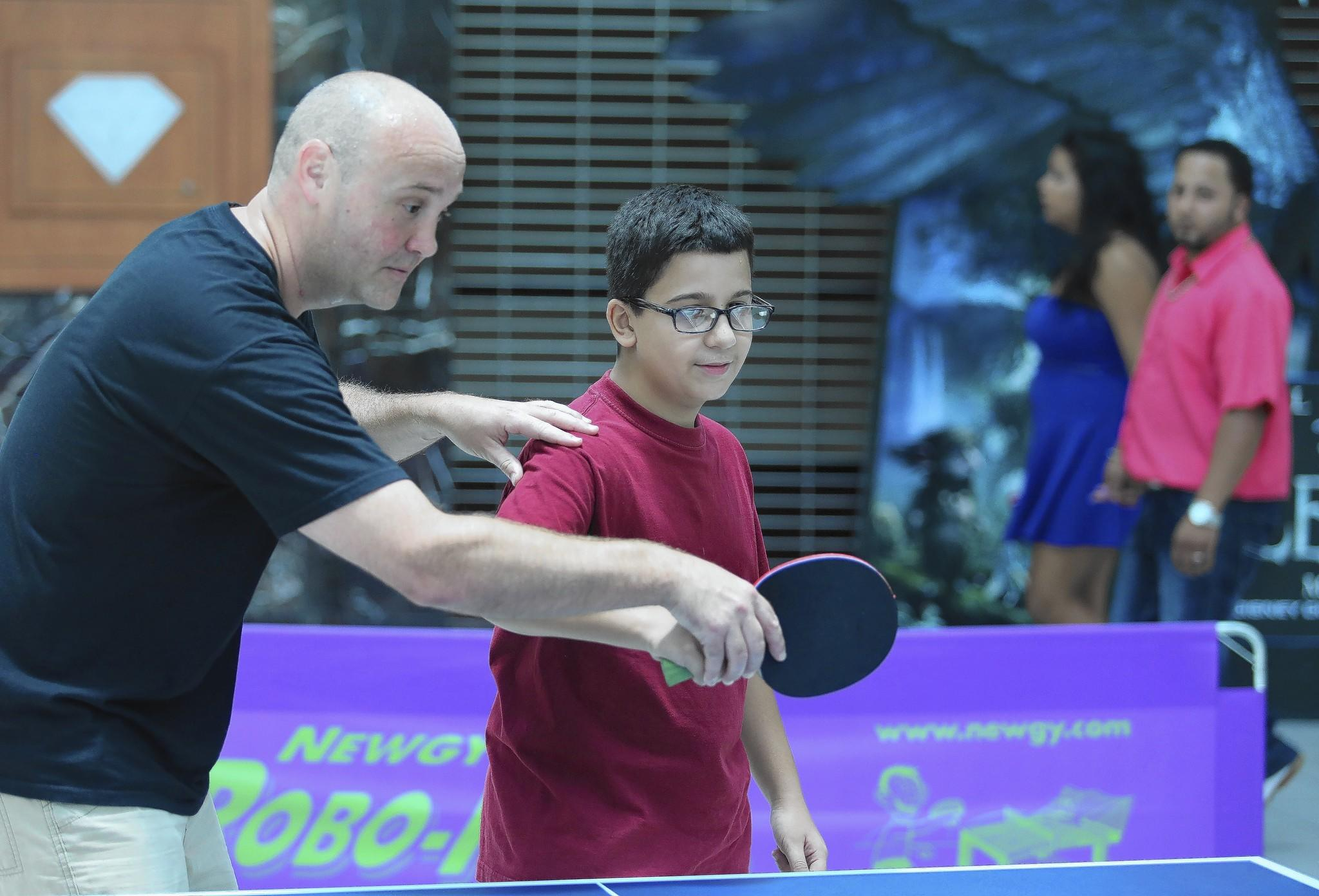 Alex Martinez-Torres, visiting from Puerto Rico, tries table tennis for the first time, with coaching from Michael McFarland.