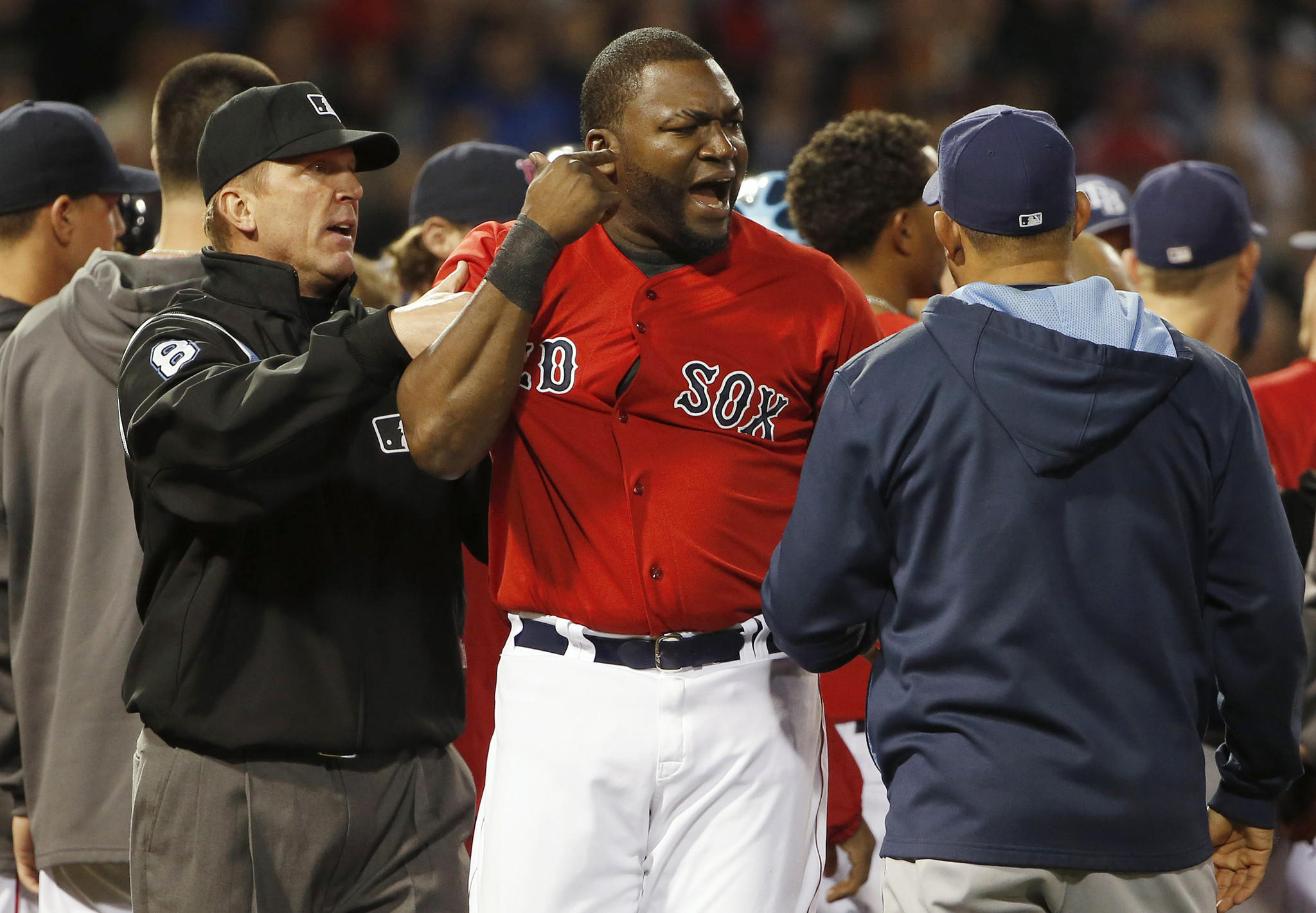 David Ortiz #34 of the Boston Red Sox is contained by an unidentified Tampa Bay Ray and umpire Jeff Kellogg #8 after teammate Mike Carp #37 of the Boston Red Sox was hit by a pitch during the fourth inning of the game at Fenway Park on May 30, 2014 in Boston.