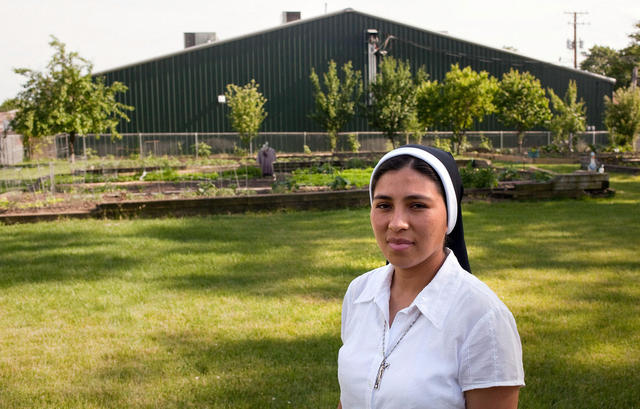 Sister Almarosa, of Missionary Sisters of St. Charles Borromeo, stands in the convent's garden, with Club Allure in the background. The group of nuns is suing the strip club.
