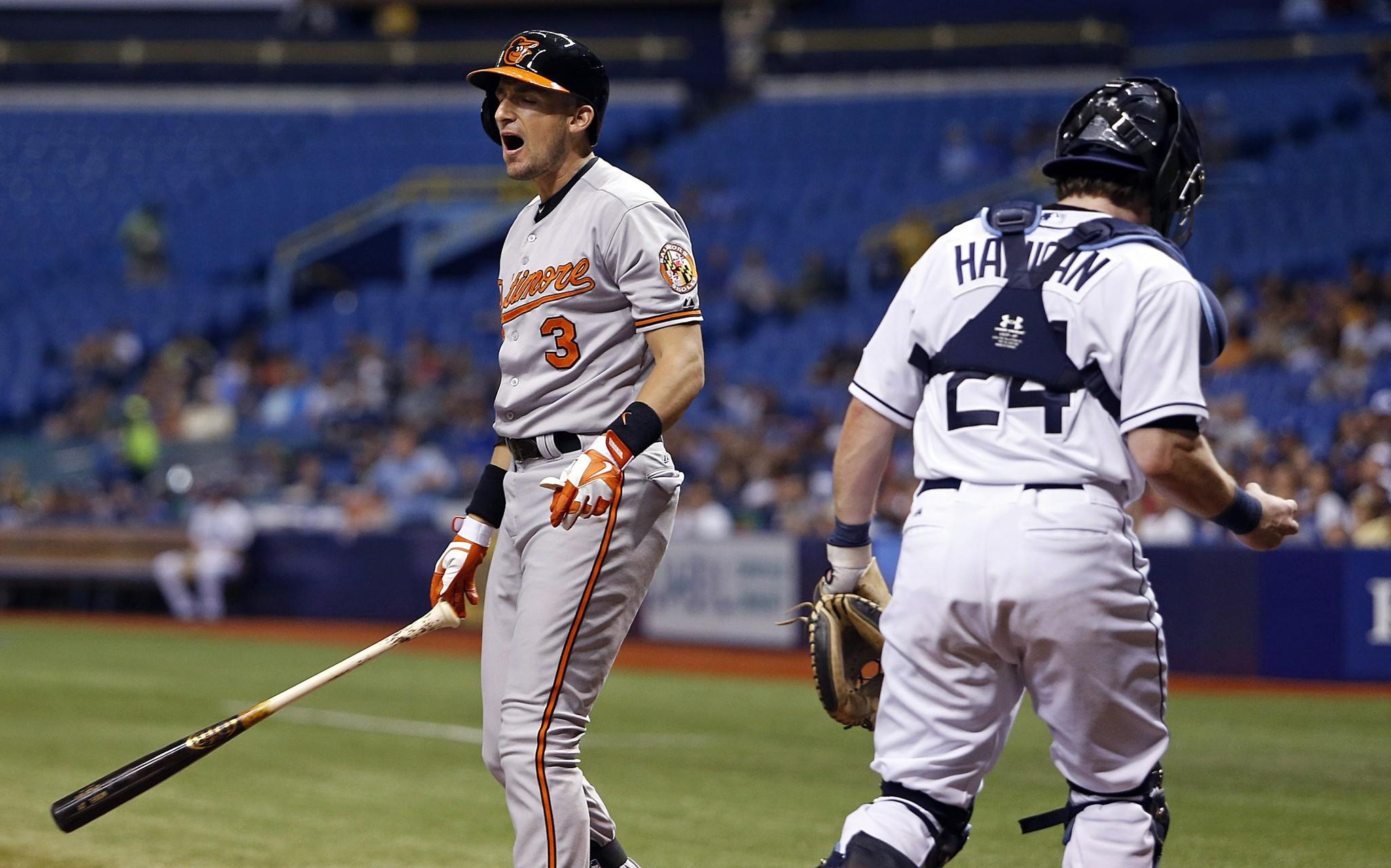 Orioles infielder Ryan Flaherty reacts as he strikes out swinging in front of catcher Tampa Bay Rays catcher Ryan Hanigan with two men on base to end the top of the second inning at Tropicana Field in St. Petersburg, Fla.