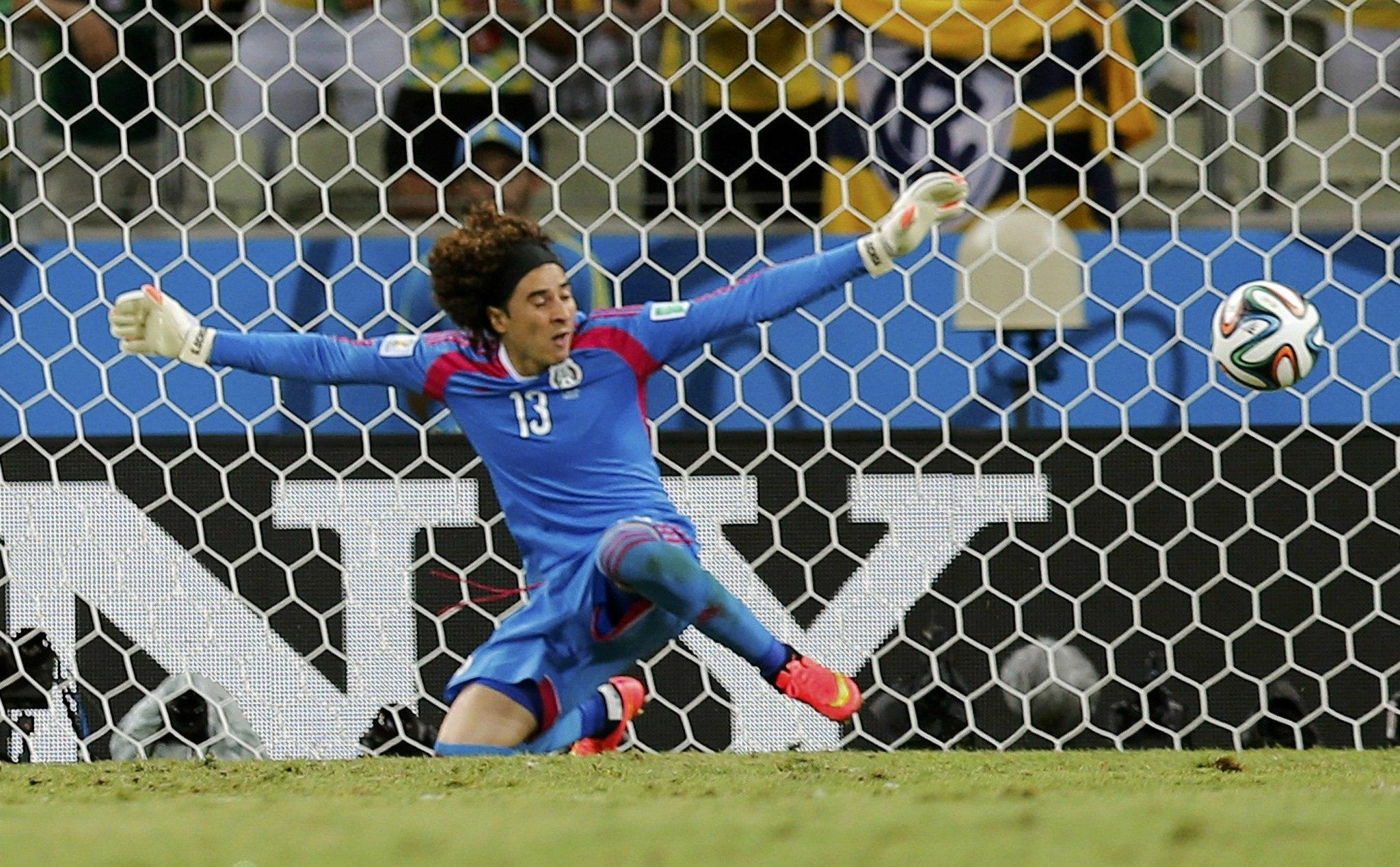 Mexico's goalkeeper Guillermo Ochoa makes a save during the 2014 World Cup Group A soccer match against Brazil.