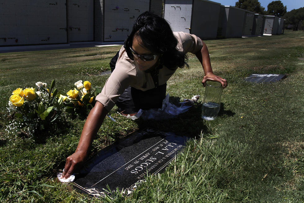 LaQuita Suggs cleans her mother's headstone at the Inglewood Park Cemetery on the seventh anniversary of her death.