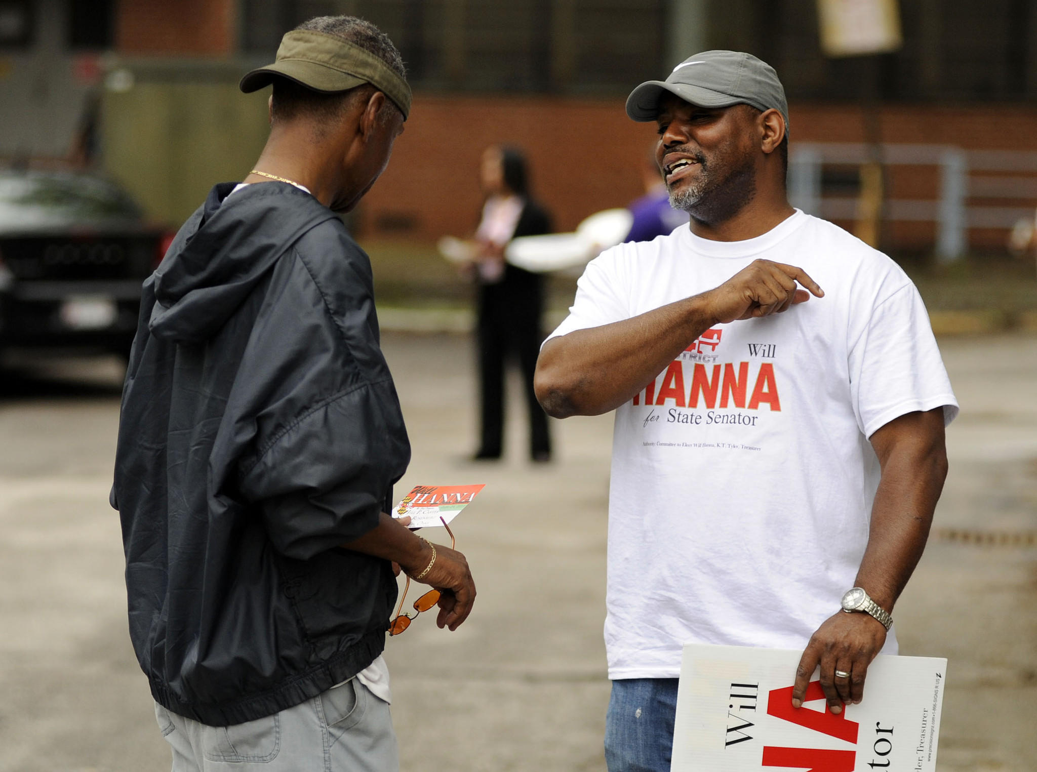 Will Hanna, a candidate for State Senator, speaks to Nathaniel Evans Jr. before he heads into cast his vote at an early voting center at the Public Safety Training Facility in Baltimore. Hanna is wanted on charges of theft in Texas.