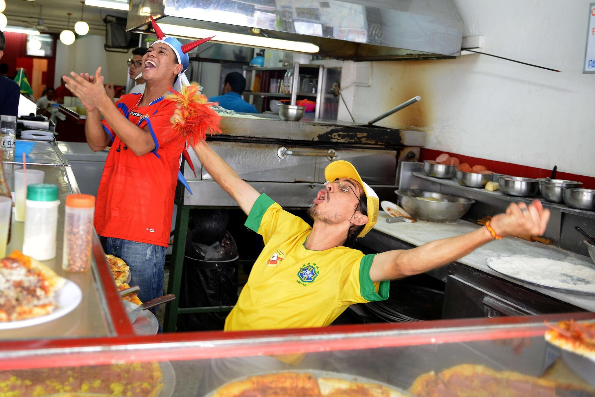 Workers at a pizza store in San Jose celebrate Costa Rica's goal against Uruguay in the World Cup.