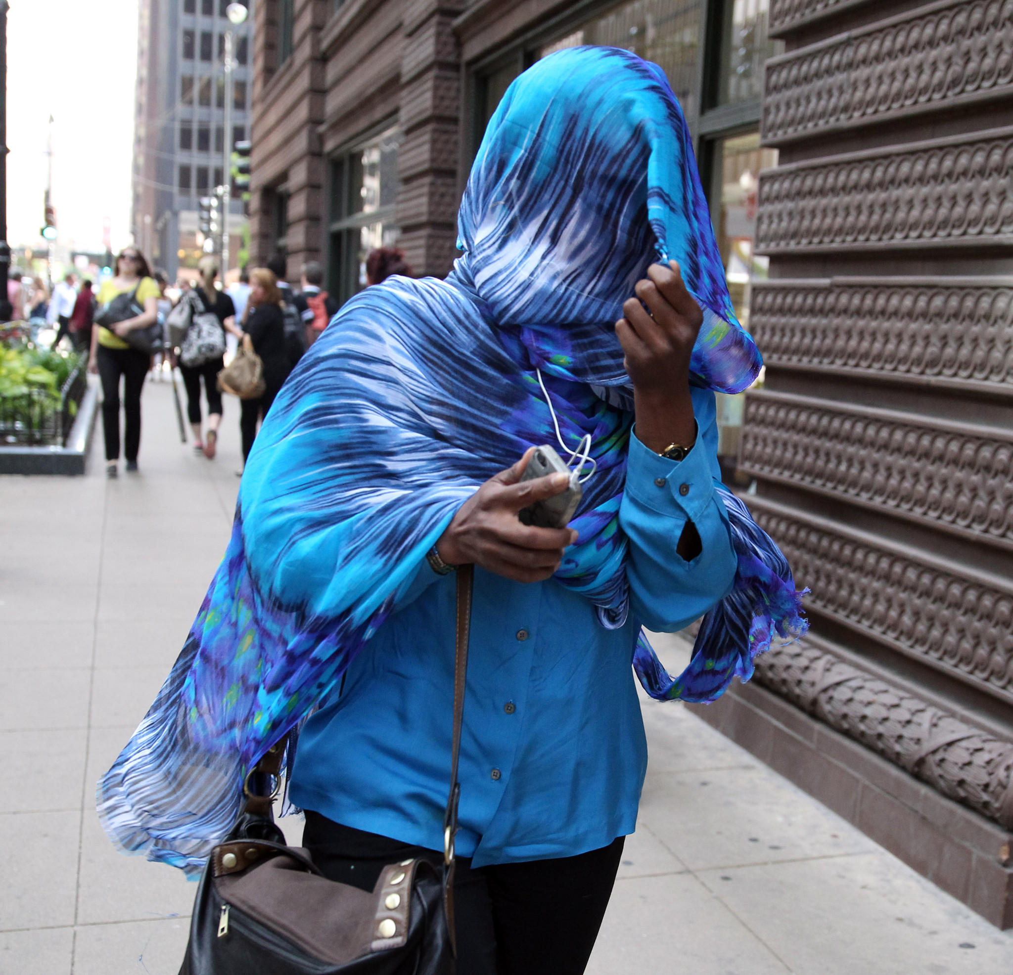 Using a scarf to obscure her face, Cherron Phillips leaves the Dirksen U.S. Courthouse in Chicago on Monday.