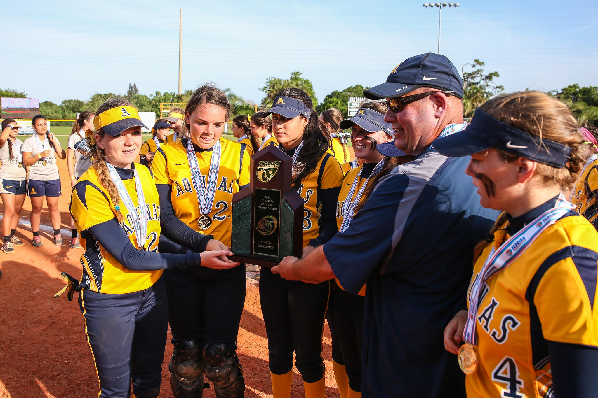 St. Thomas Aquinas Raiders seniors receive the trophy for winning the Class 7A softball title.
