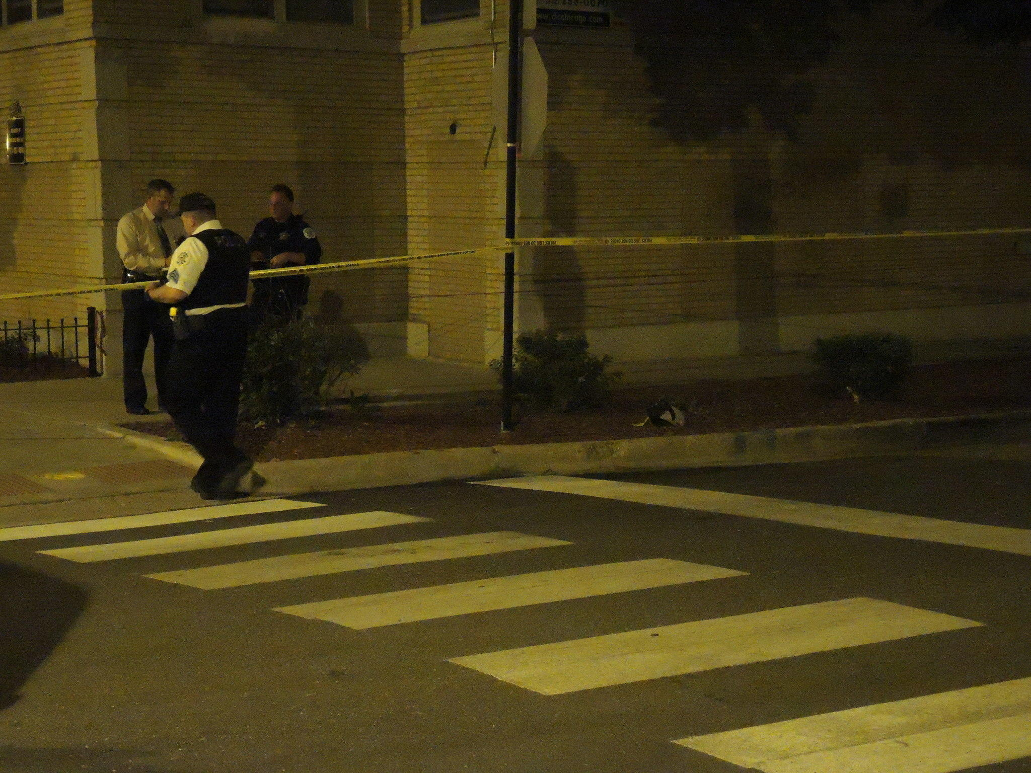Police investigate the scene where a 14-year-old boy was critically injured by a gunshot wound to the back.