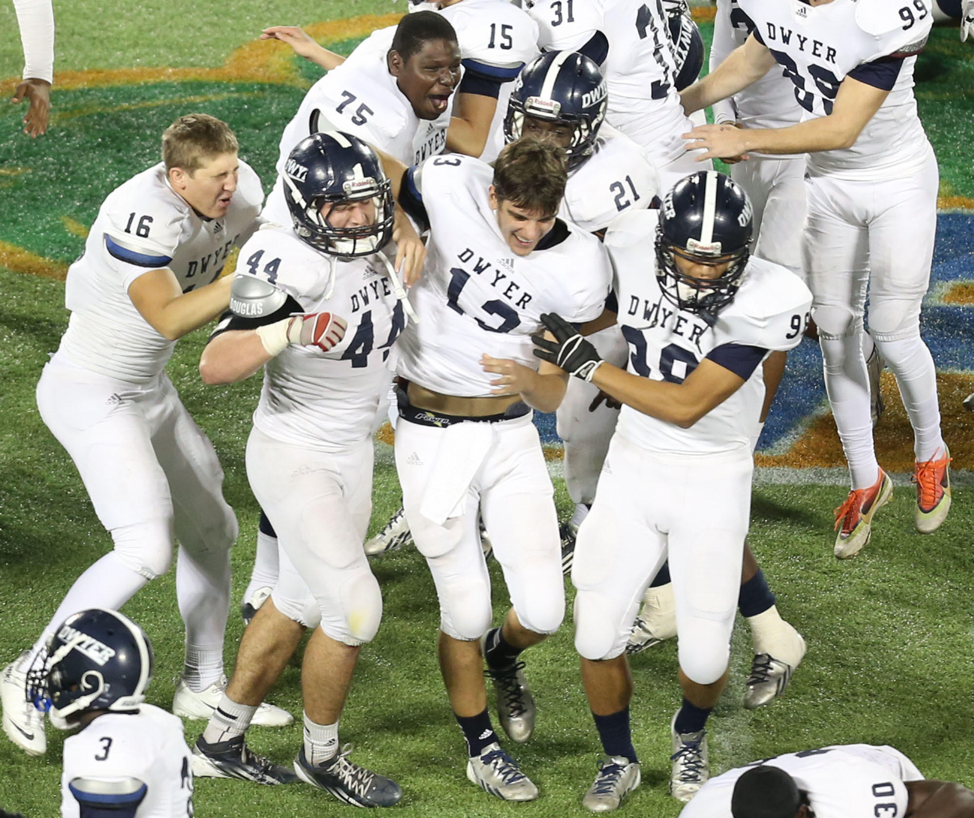 Dwyer players celebrate on the field after winning the Class 7A state football championship.