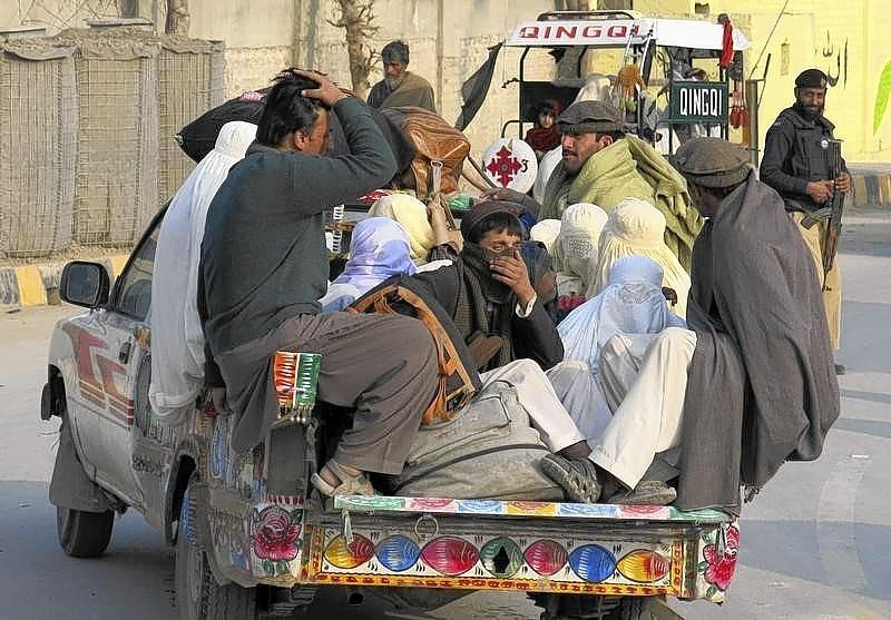 Families sit in the back of a vehicle as they flee a military offensive against the Pakistani Taliban.
