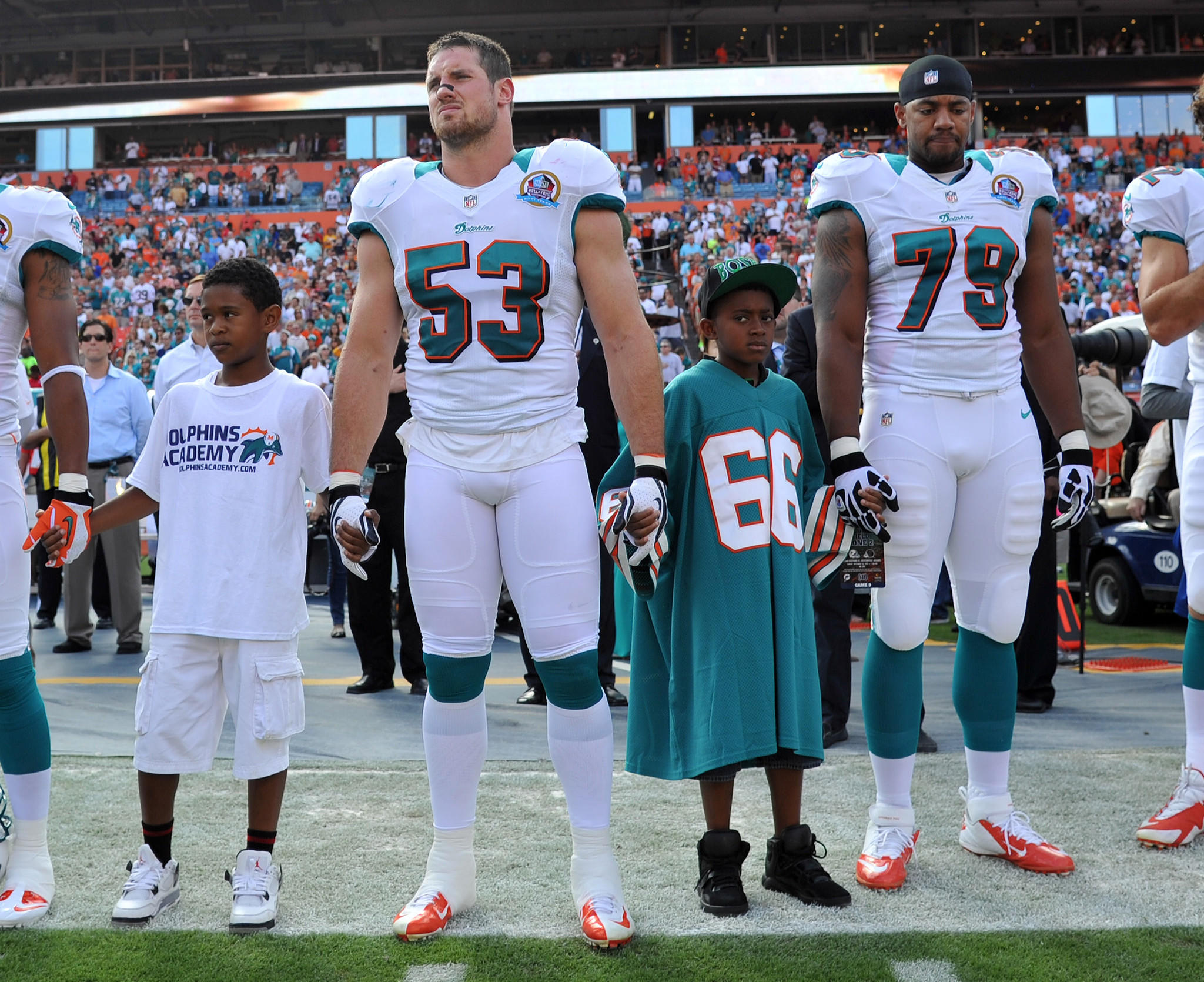Former Miami linebacker Austin Spitler (53) holds children's hands during a moment of silence in 2012.