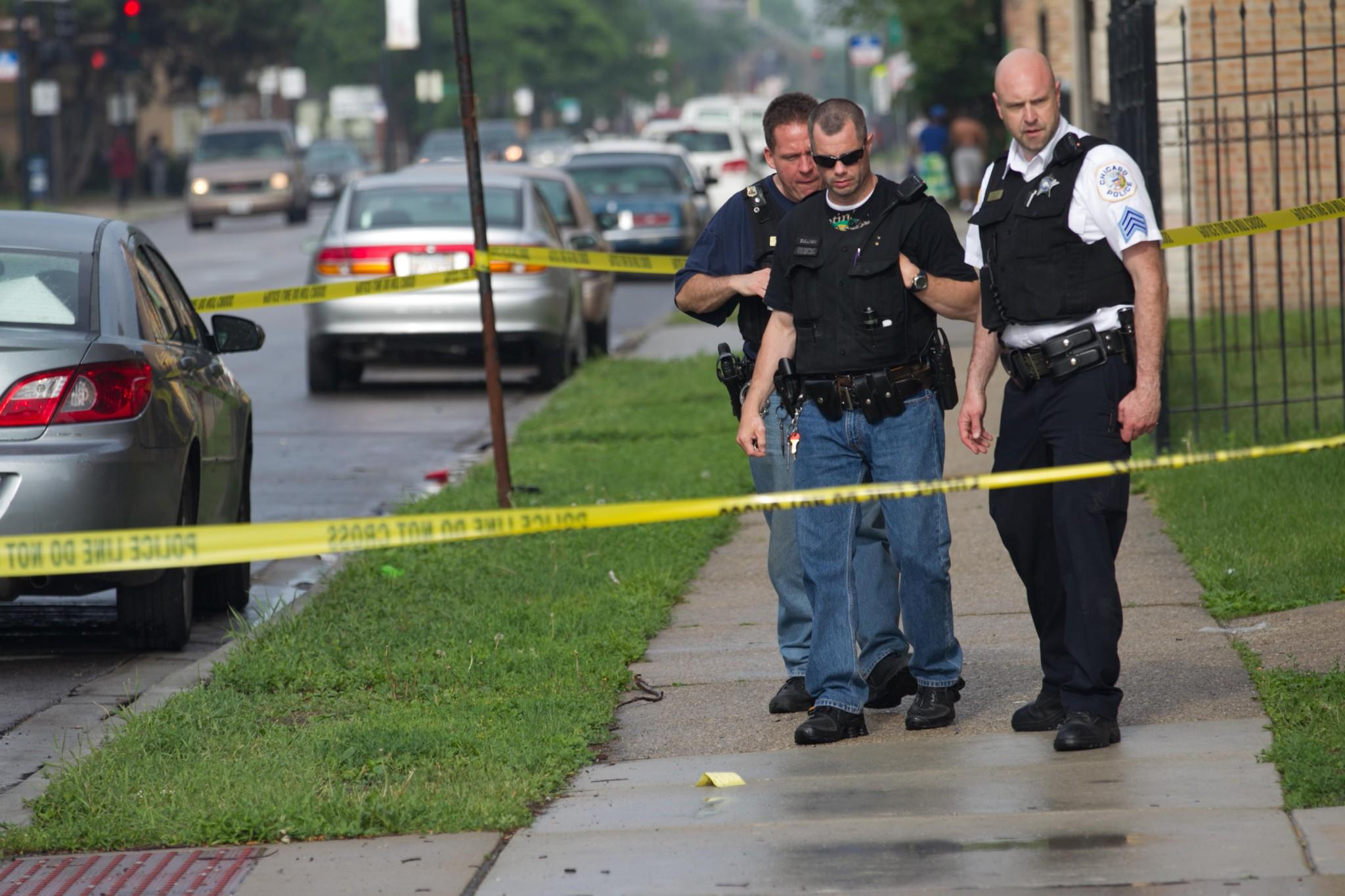 Police investigate a shooting at the corner of 71st Street and Francisco Avenue in Chicago on Thursday.