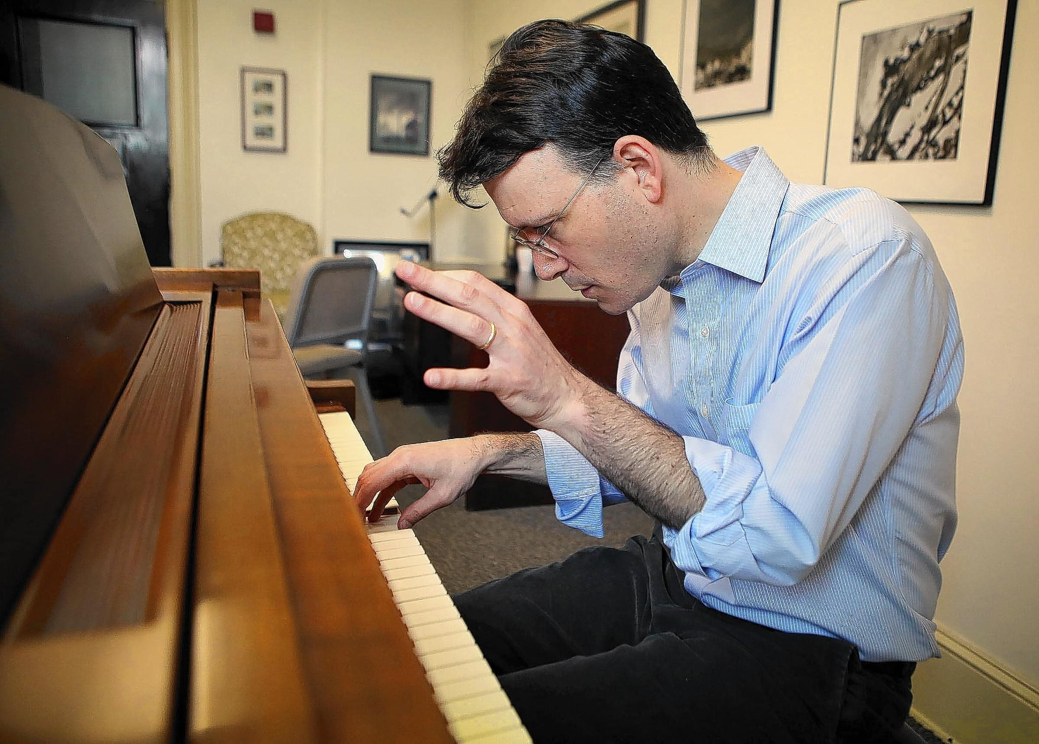 Composer and teacher Michael Hersch plays a selection from the opening song of his opera in his studio at the Peabody Institute.