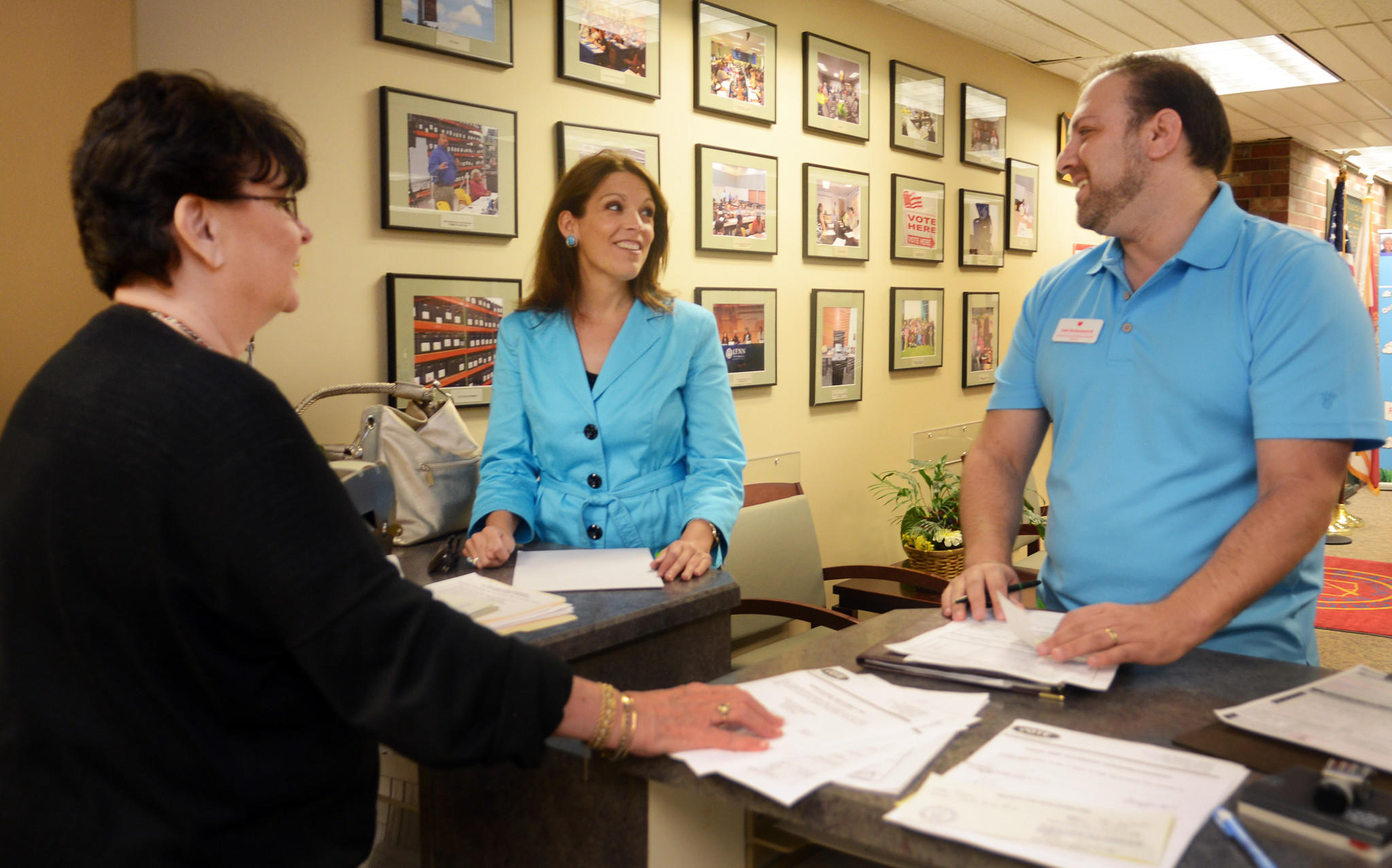 Supervisor of Elections Office Public Services Director (left) Mary Cooney takes the paperwork from (middle) Gineen M. Bresso, running for Broward Soil & Water Conservation District 4, and (right) Sam Budyszewick, running for Broward County School Board District 3, so they can qualify to appear on the ballot Friday less hour before the noon Friday deadline in Fort Lauderdale. Photo by Taimy Alvarez, Sun Sentinel