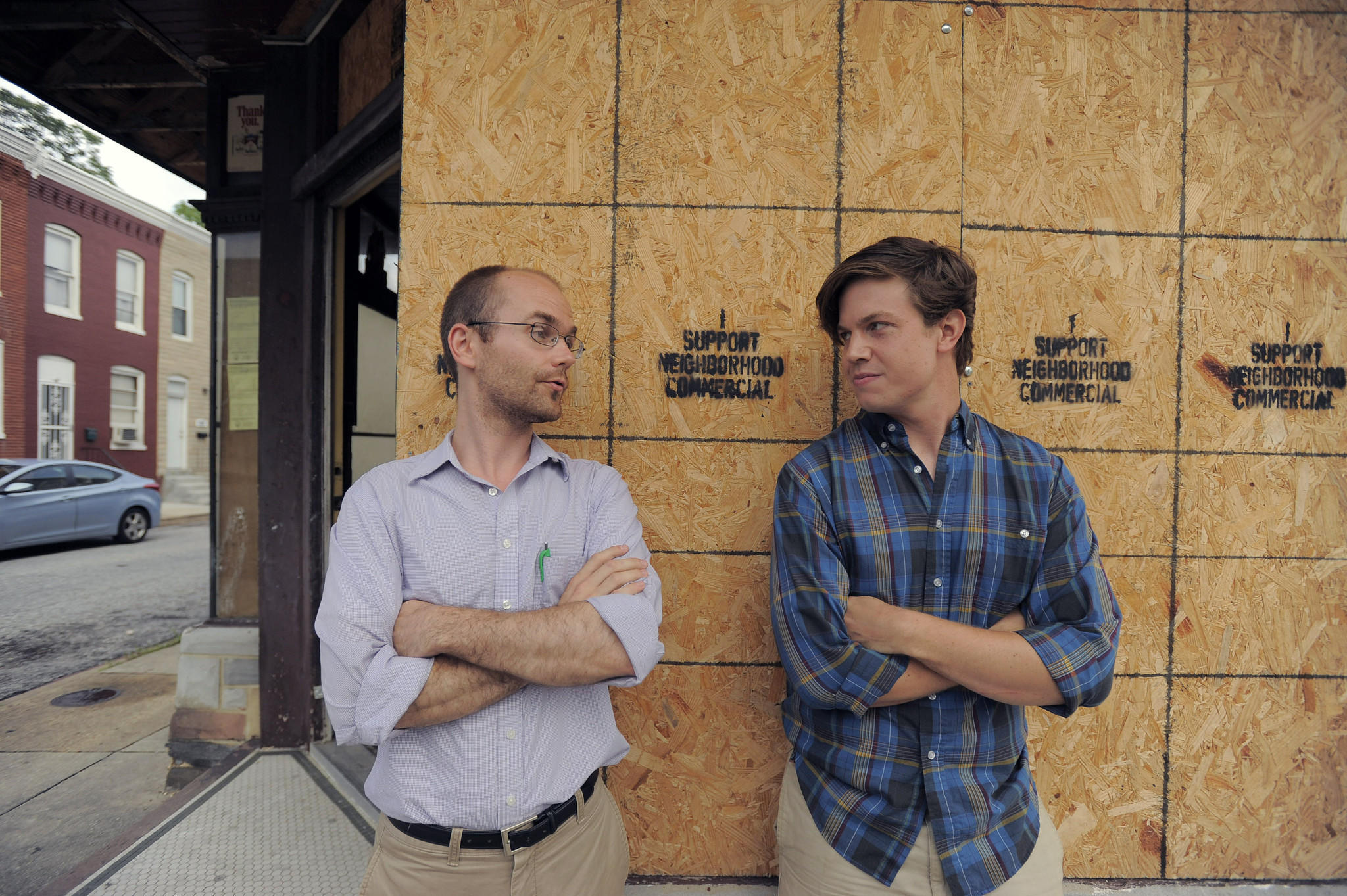 Peter Burkill (left) and Ryan Flanigan talk about a structure that was once a corner store in Remington. Burkill, his wife and two other neighbors bought the vacant property and want to make it into a coffee shop or inexpensive restaurant.