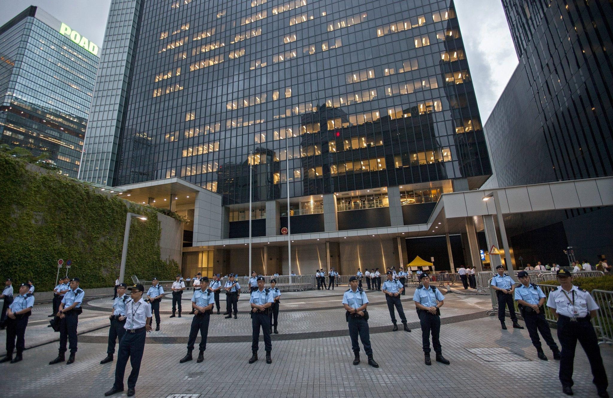 Police stand guard outside the Hong Kong government headquarters as hundreds of protesters protest the development plan of three new towns in Hong Kong's North East New Territories along the border with China, outside the Hong Kong government headquarters, Hong Kong June 20, 2014.