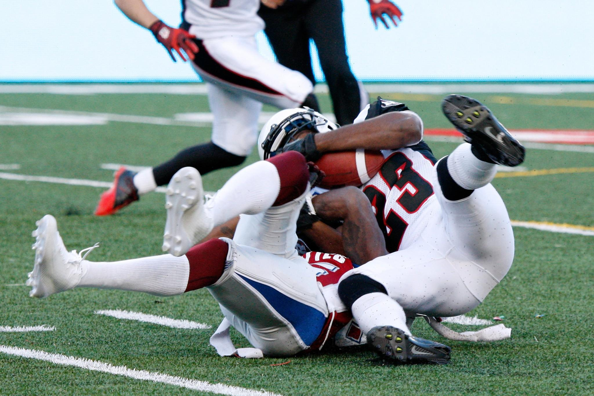 Seth Williams of the Ottawa Redblacks, right, wrestles for the ball with Chad Johnson of the Montreal Alouettes during the CFL game at Percival Molson Stadium on June 20, 2014 in Montreal, Quebec, Canada.