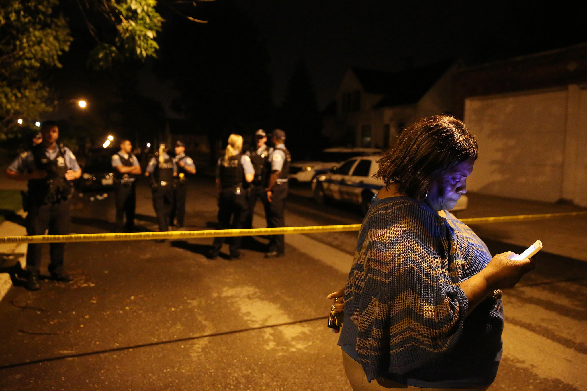 A woman who identified herself as an aunt of a 15-year-old homicide victim stands nearby as police work the scene Saturday, June 21, 2014 at the intersection of West 109th Place and South Perry Avenue in Chicago.