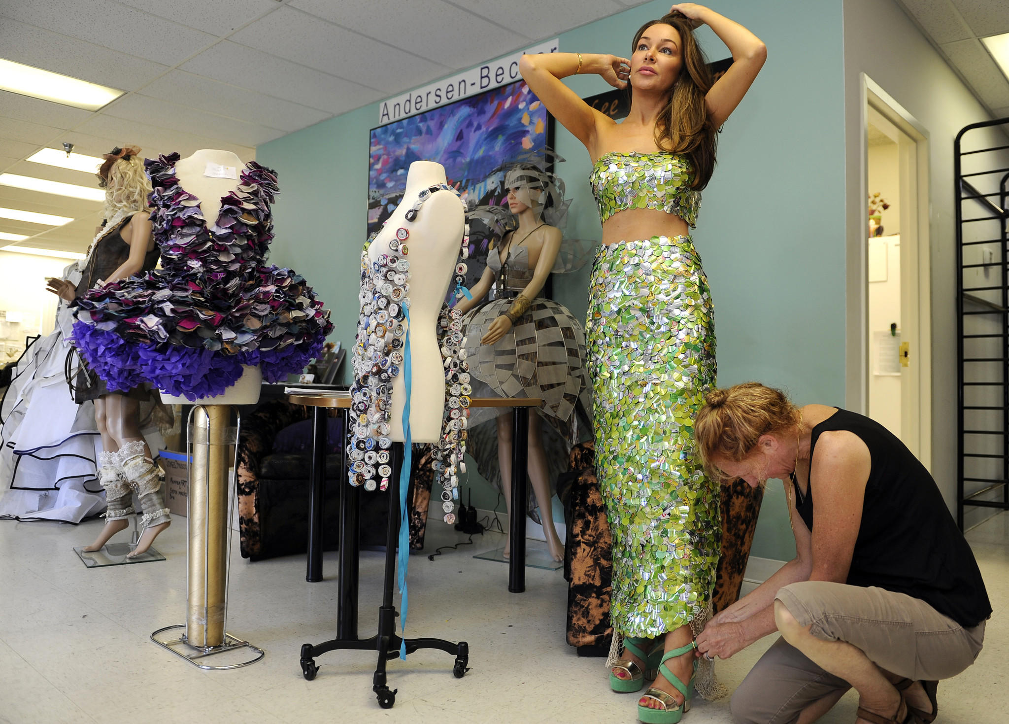 "Laurel, MD--June 17, 2014--Model Gretchen Kuppers of Baltimore, who is wearing a ""Metal Mermaid"" outfit which is made with soda can pieces, gets help buckling her shoes from Lee Andersen, right, a fashion designer and founder of ManneqART. Ms. Andersen runs an annual contest for hair and makeup artists and wearable art designers. This morning models were trying on some of the outfits that will be worn in the competition on Sunday."