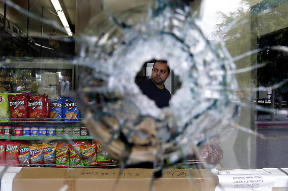 Seen through a bullet hole, IV Deli Mart owner Michael Hassan cleans up his store near UC Santa Barbara. A gunman fatally shot someone there.