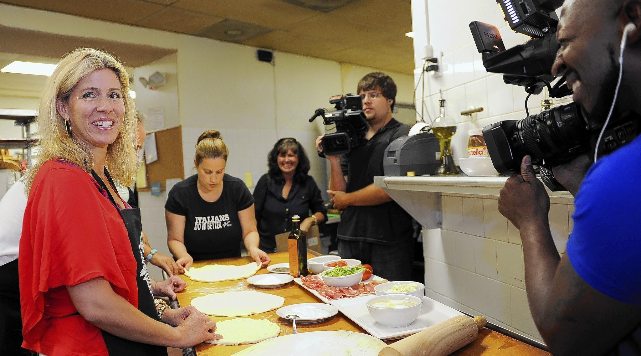 "A crew from city-owned TV 25 tapes a segment for the new show ""Tasty Travels"" at DiPasquale's deli in East Baltimore. Here, show host Kate Beck gets ready to shoot a pizza-making scene. Camera operator Mike Wells is on right."