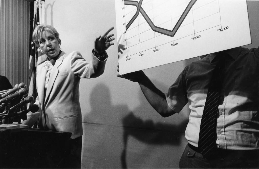 Former Mayor Jane Byrne challenges then-Mayor Harold Washington's record on female hiring at a news conference on Jan. 20, 1987, as her Communications Director Joe Pecor holds up charts that support her figures.