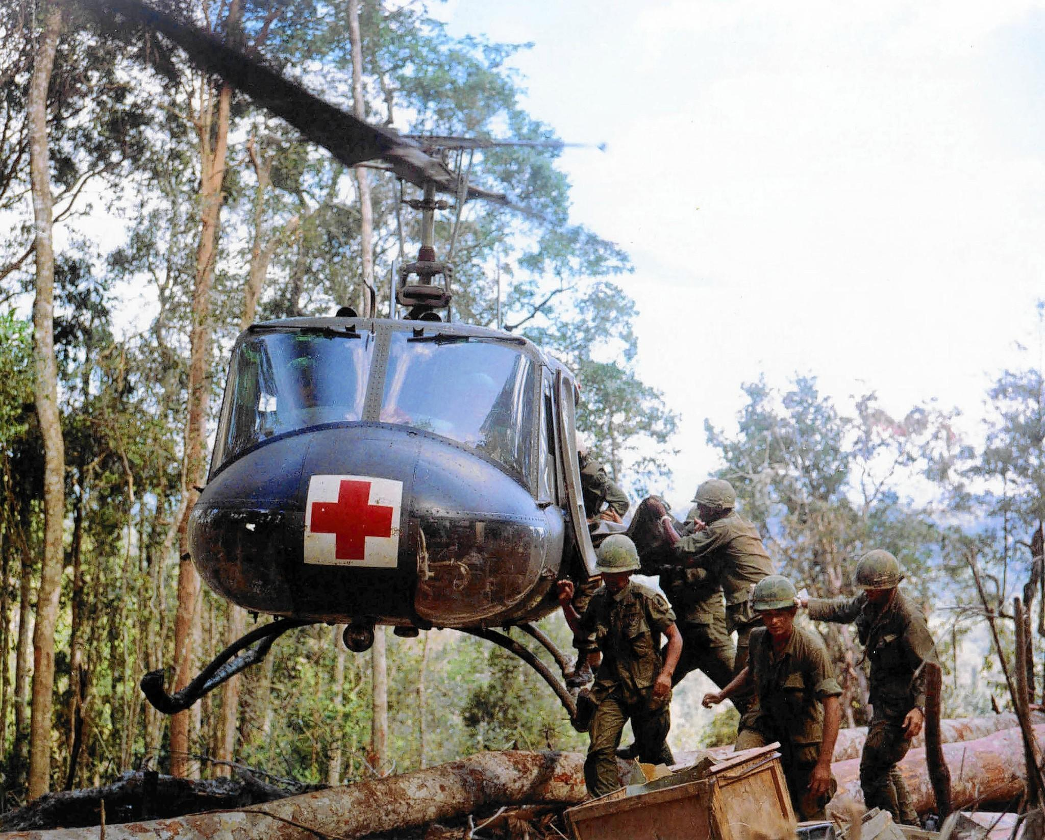 Members of the 173rd Airborne Brigade load casualties onto a helicopter in Vietnam in November 1967 for evacuation to a field hospital.