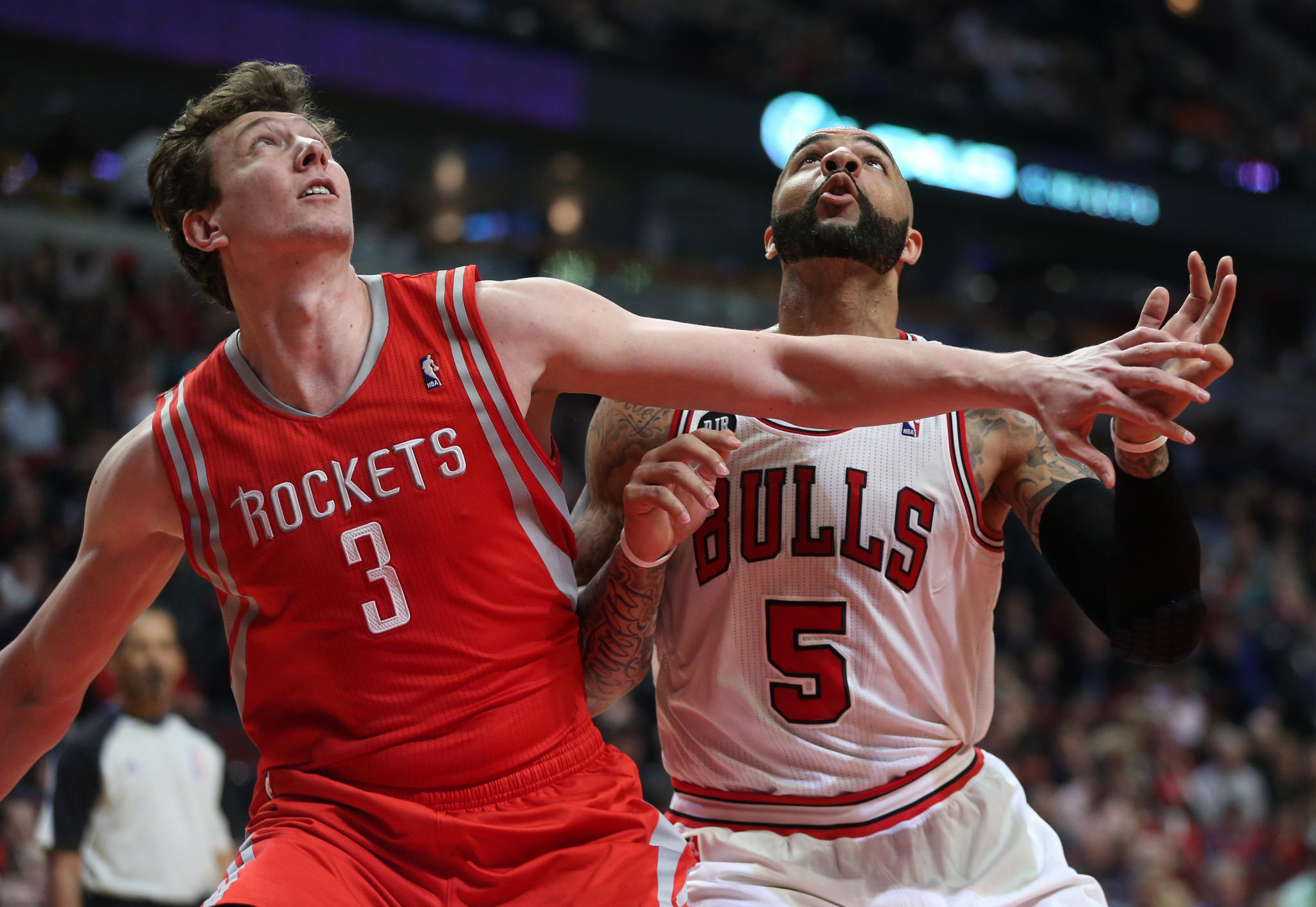 The Rockets' Omer Asik and the Bulls' Carlos Boozer fight for position on a rebound in the first half at the United Center.
