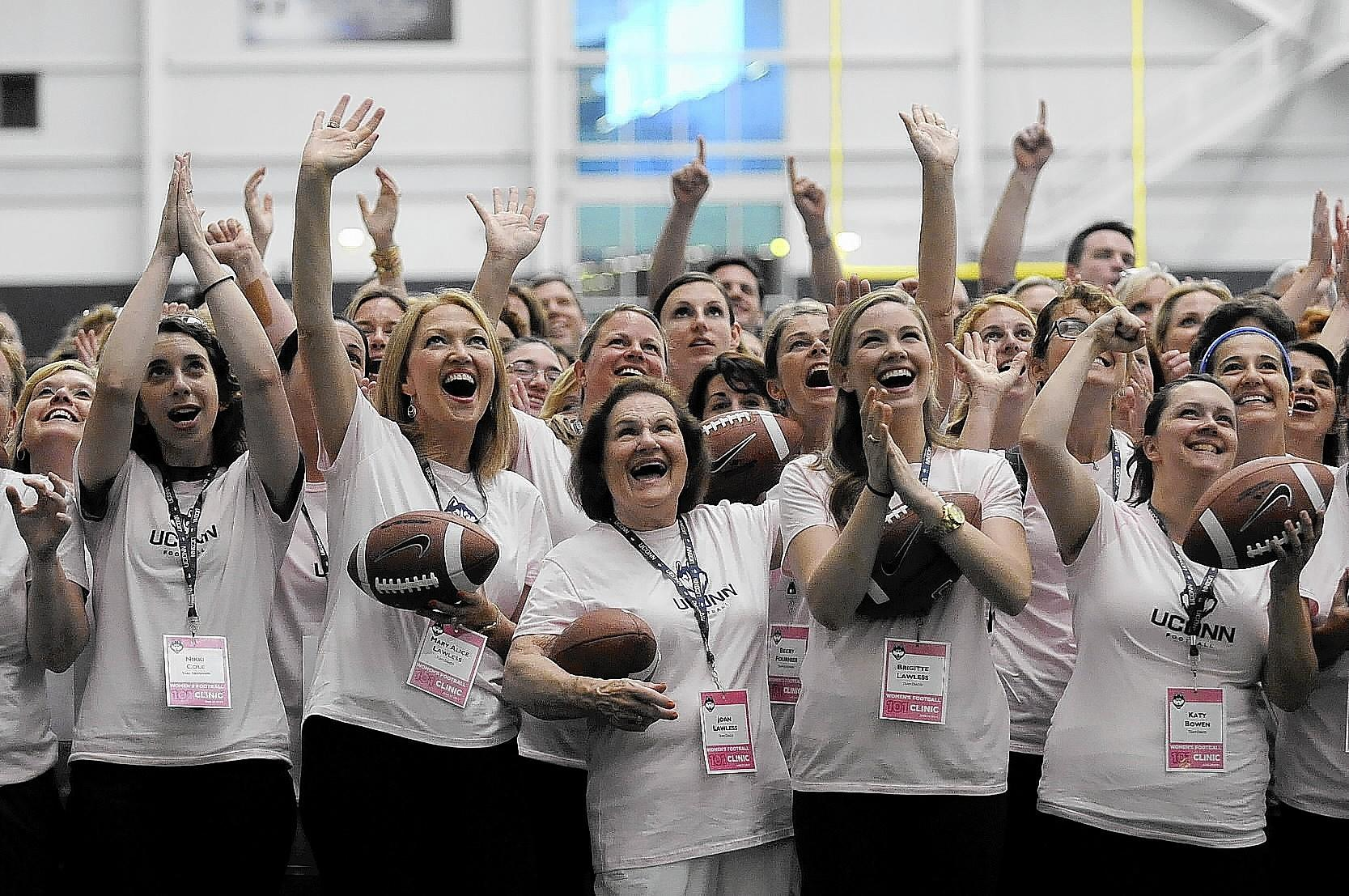 More than 200 women attended a football clinic run by the UConn football team Wednesday night at the Shenkman Center, including Joan Lawless, at center, who was celebrating her 80th birthday. With are her daughter-in-law Mary Alice, at left, and niece Brigette, at right. Mary Alice's daughter Sarah is the Director of Football Operations at UConn. The Lawless family drove up from Morristown, NJ.