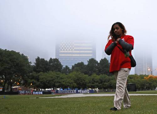 Aurel Phillips walks through the Petrillo Music Shell lawn after finishing her overnight security post of guarding the area in preparation for the viewing of the World Cup match between the U.S. and Germany.