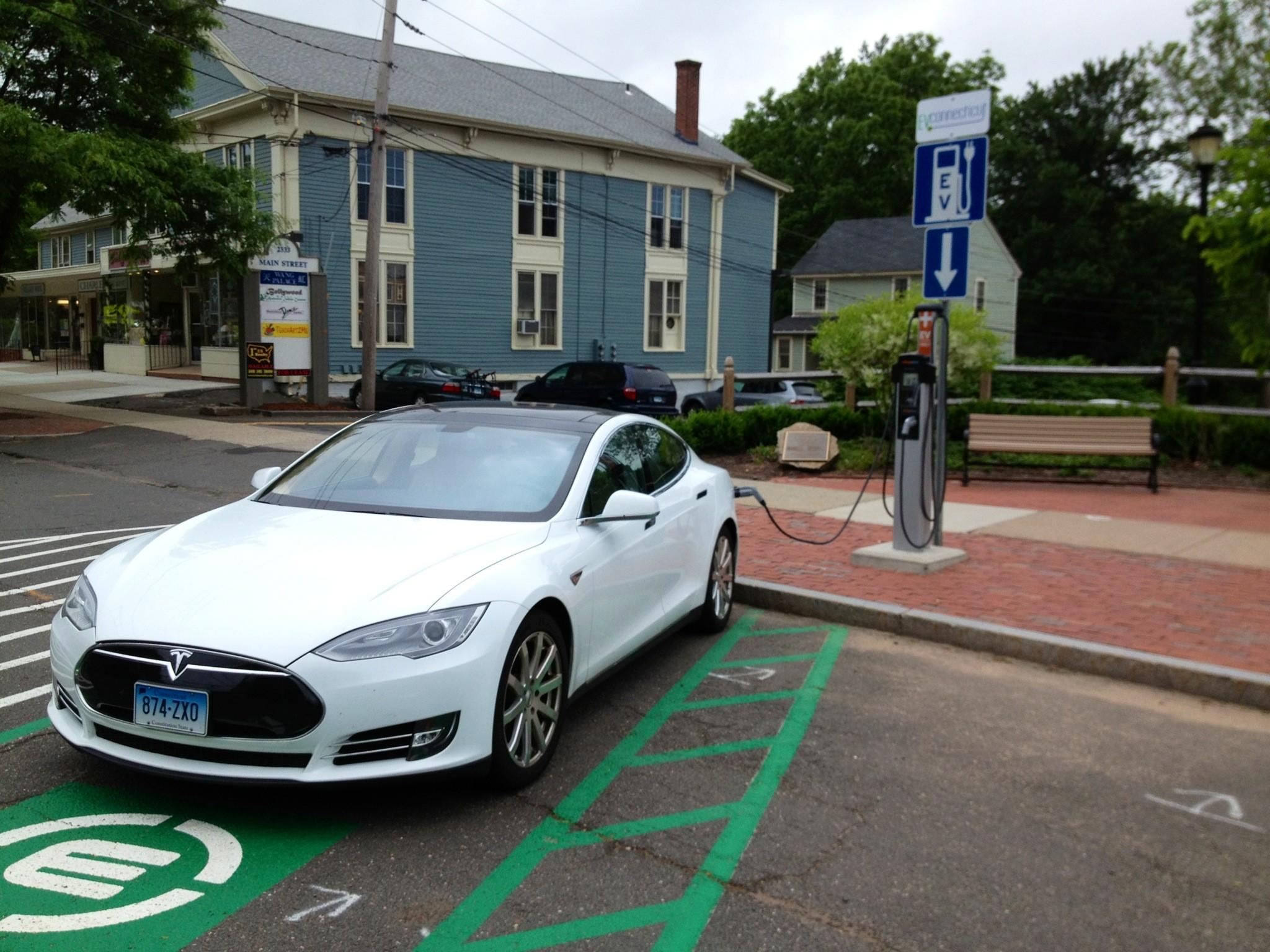 An electric car owner takes advantage of the electric charging station recently installed along Main Street.