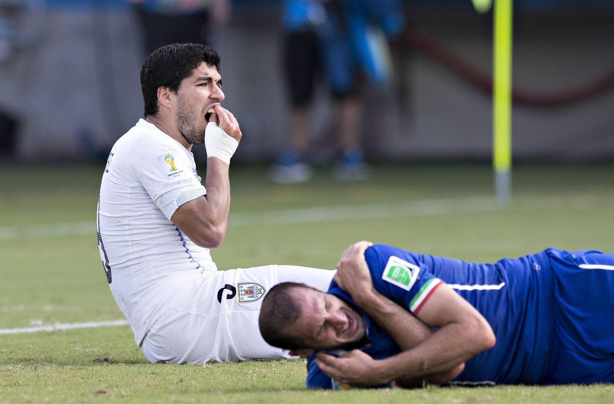 Luiz Suarez of Uruguay touches his teeth after coming into contact with Giorgio Chiellini of Italy.