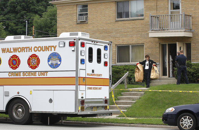 Walworth County investigators carry bags full of material from a West Allis apartment Wednesday after picking up a suspect involved in two homicides where the bodies were found in suitcases along a rural road in the Town of Geneva several weeks ago.