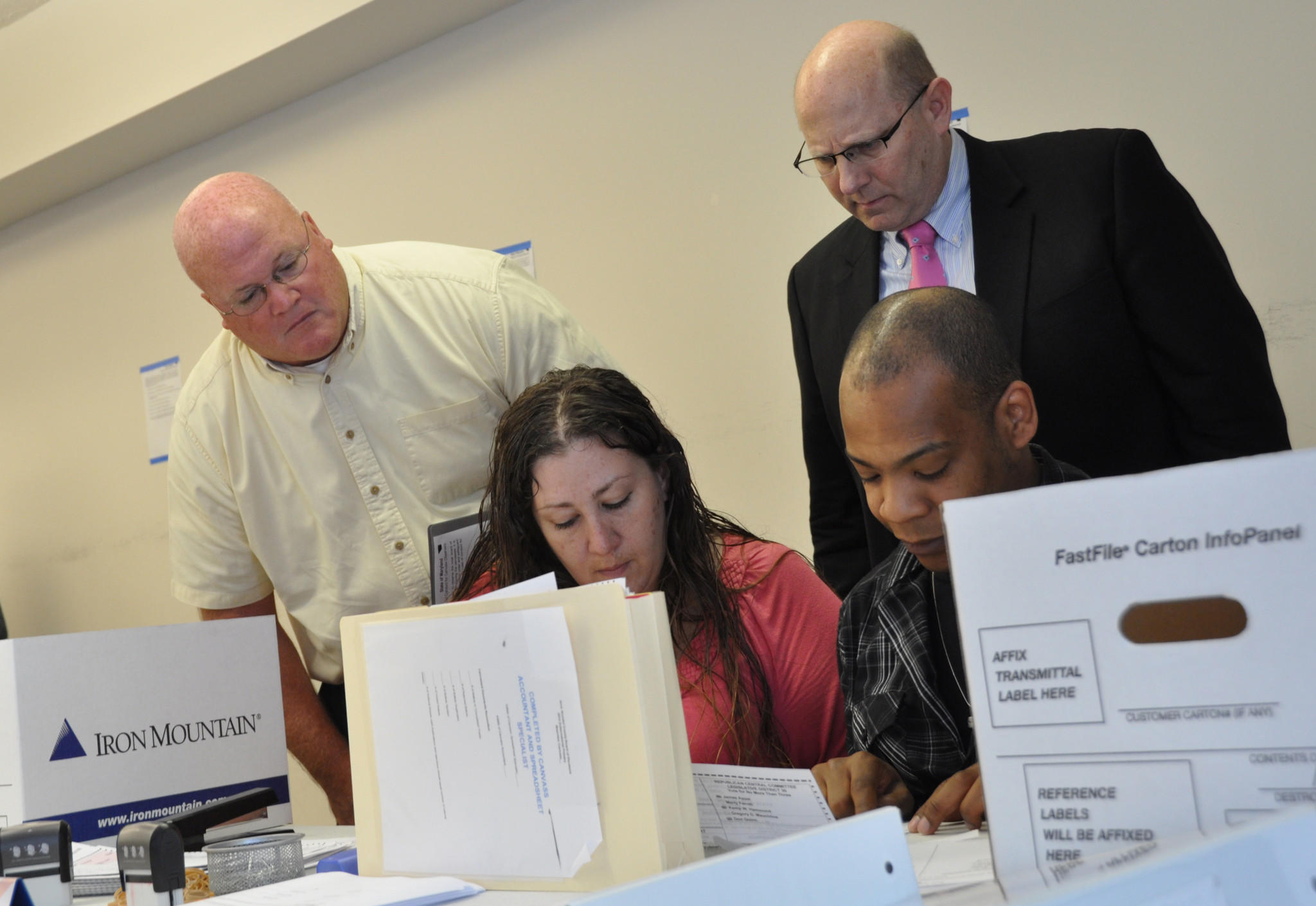 Anne Arundel County election judges Erin Treadaway, left, and Chris Singleton process absentee ballots in Glen Burnie Thursday morning. Observing the process are Phil Reeder, left, a supporter of County Council candidate Michael Anthony Peroutka, and Lawrence Scott, a consultant for Republican county executive nominee Steve Schuh. Peroutka was holding on to a slim lead over Maureen Carr-York in the Republican primary for County Council representing the Severna Park and Broadneck area.