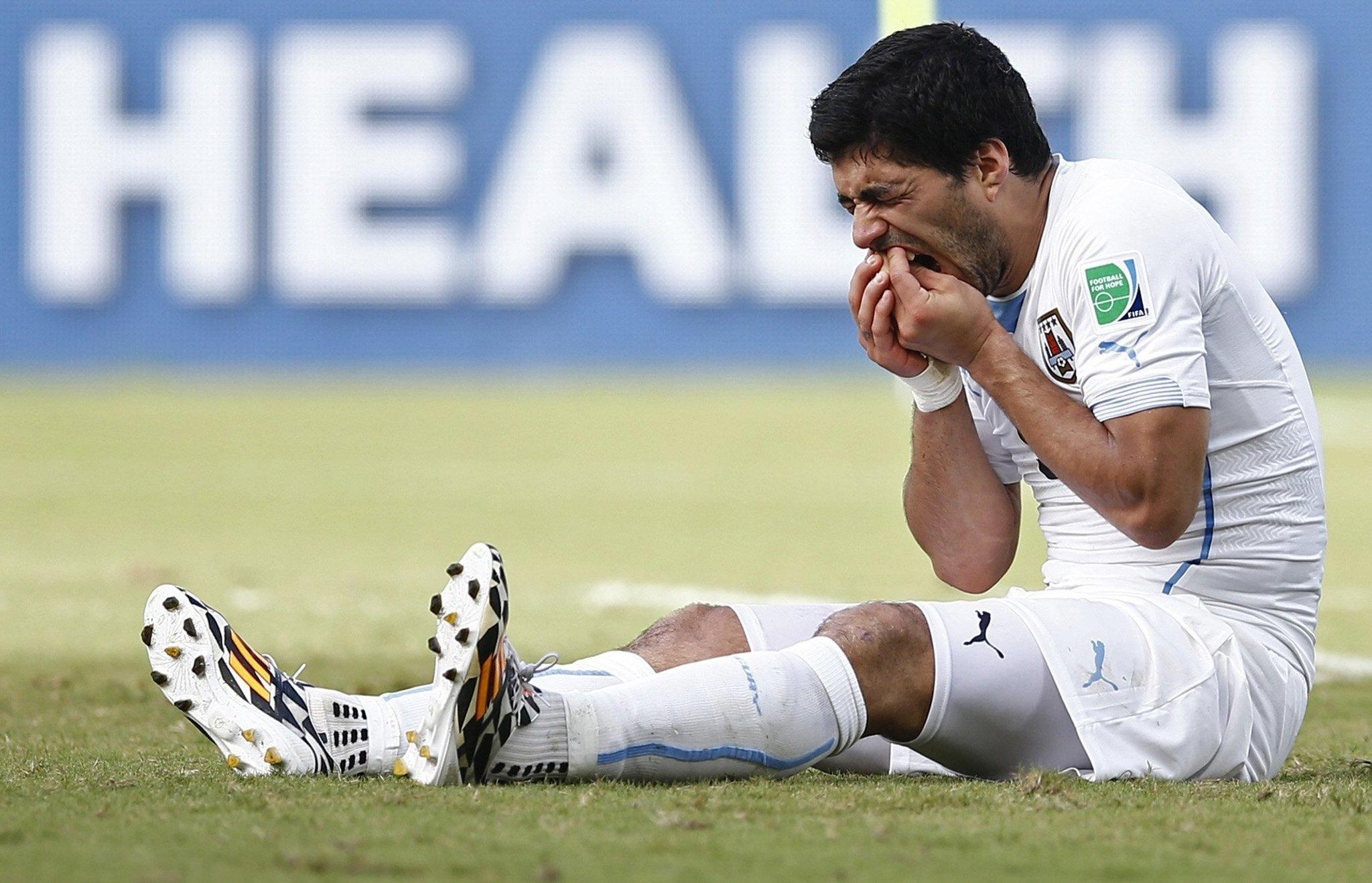 Uruguay's Luis Suarez holds his teeth after appearing to bite Italy's Giorgio Chiellini during FIFA World Cup in Natal, Brazil, on June 24, 2014.