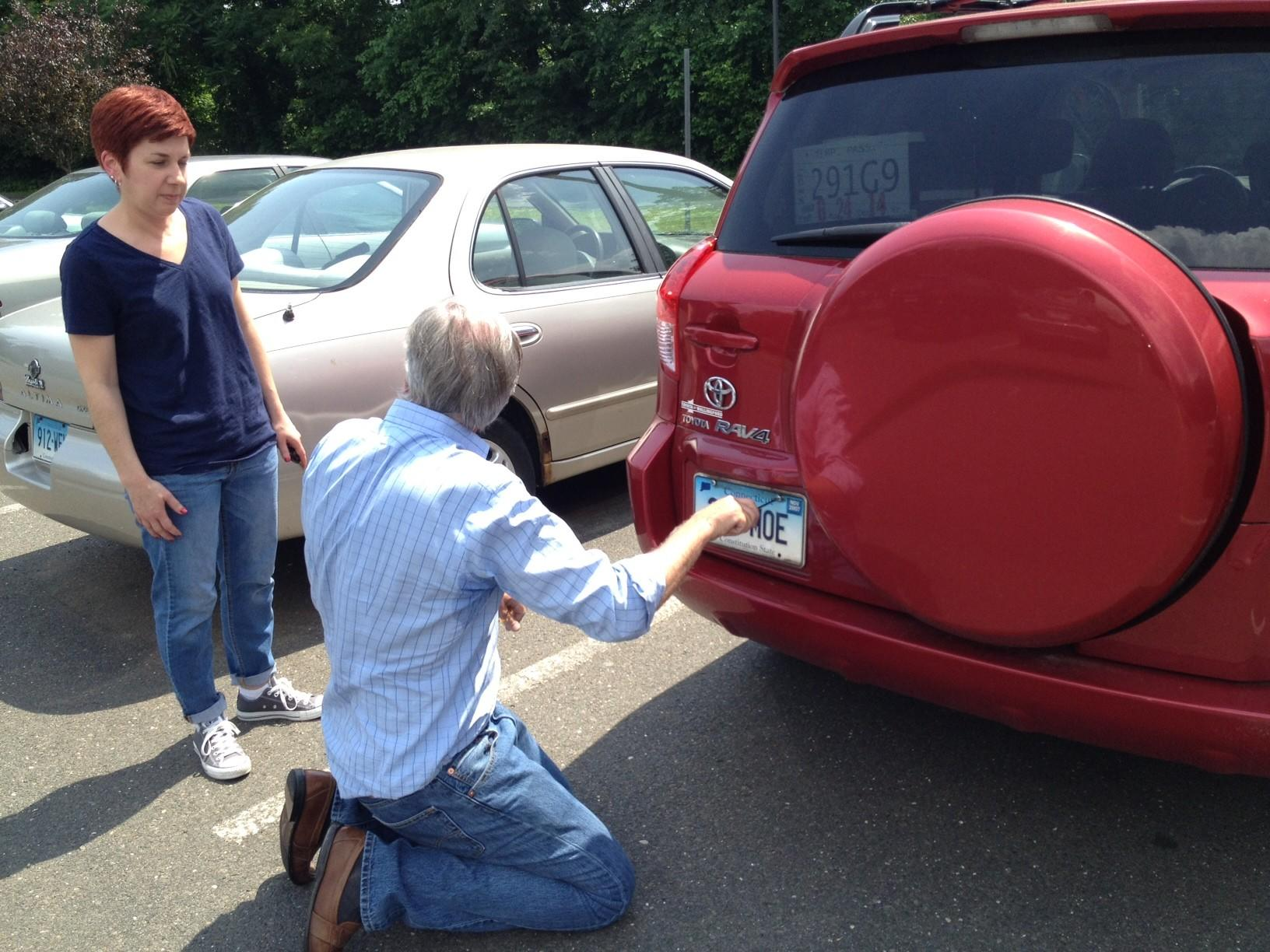Gubernatorial candidate Tom Foley helps a woman put a license plate on her car while greeting people at the Department of Motor Vehicles in New Britain.