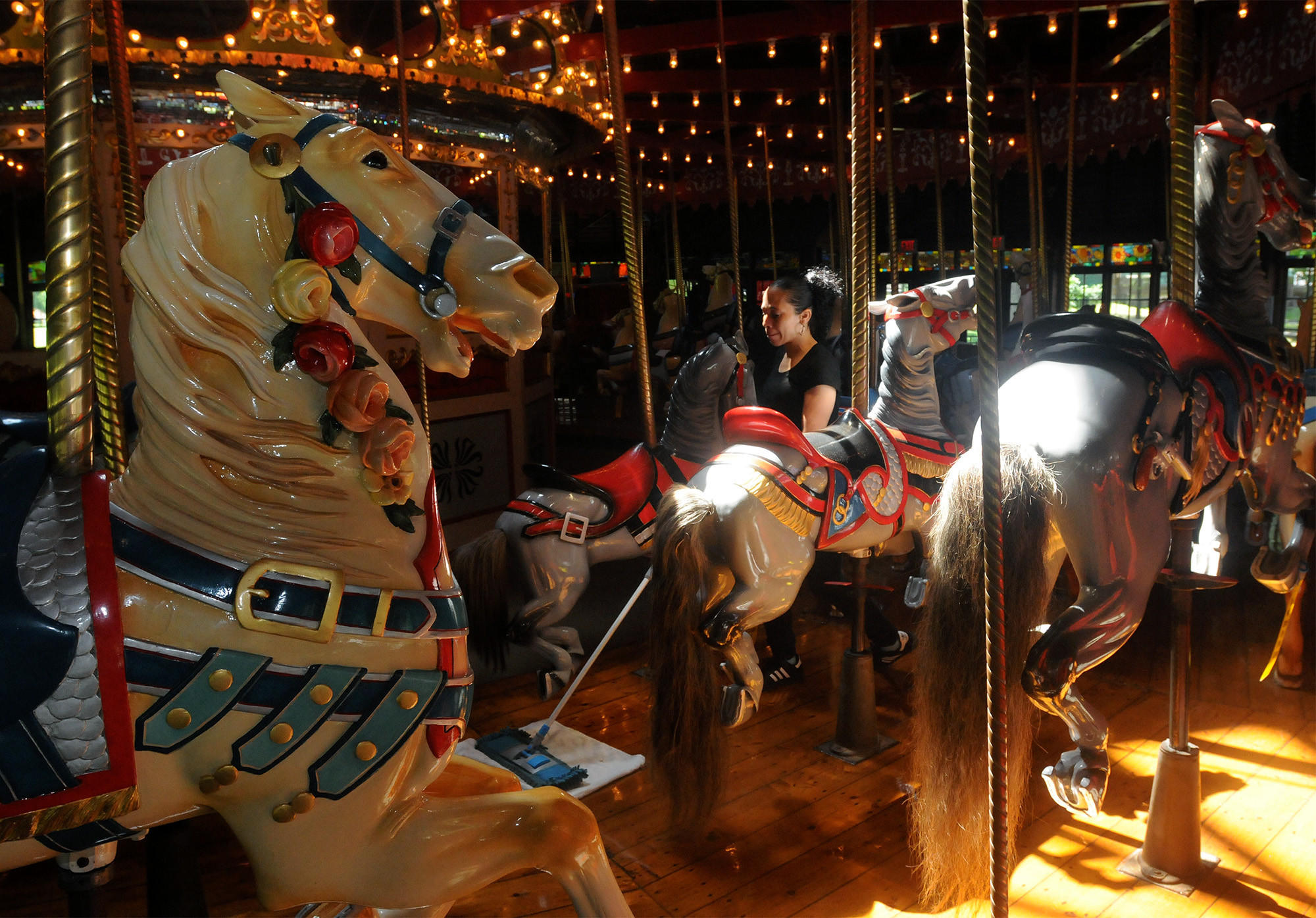 Bushnell Park Carousel employee Brenda Mendez, of Hartford, sweeps the carousel platform as part of finishing touches for tomorrow's opening day. The carousel, built in 1914, is one of three Stein and Goldstein carousels still in operation. It has been in Hartford since 1974.