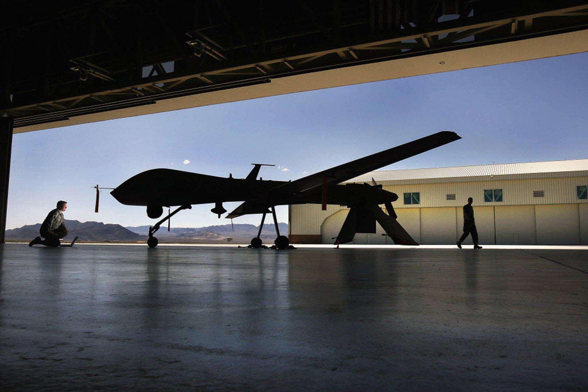 Staff Sgt. Brandon Redlich, left, uses a laptop to check on the status of a Predator unmanned aircraft system (UAS) at Creech Air Force Base in Indian Springs, Nevada. The Obama administration confirmed that U.S. armed drones are now flying over Iraq.