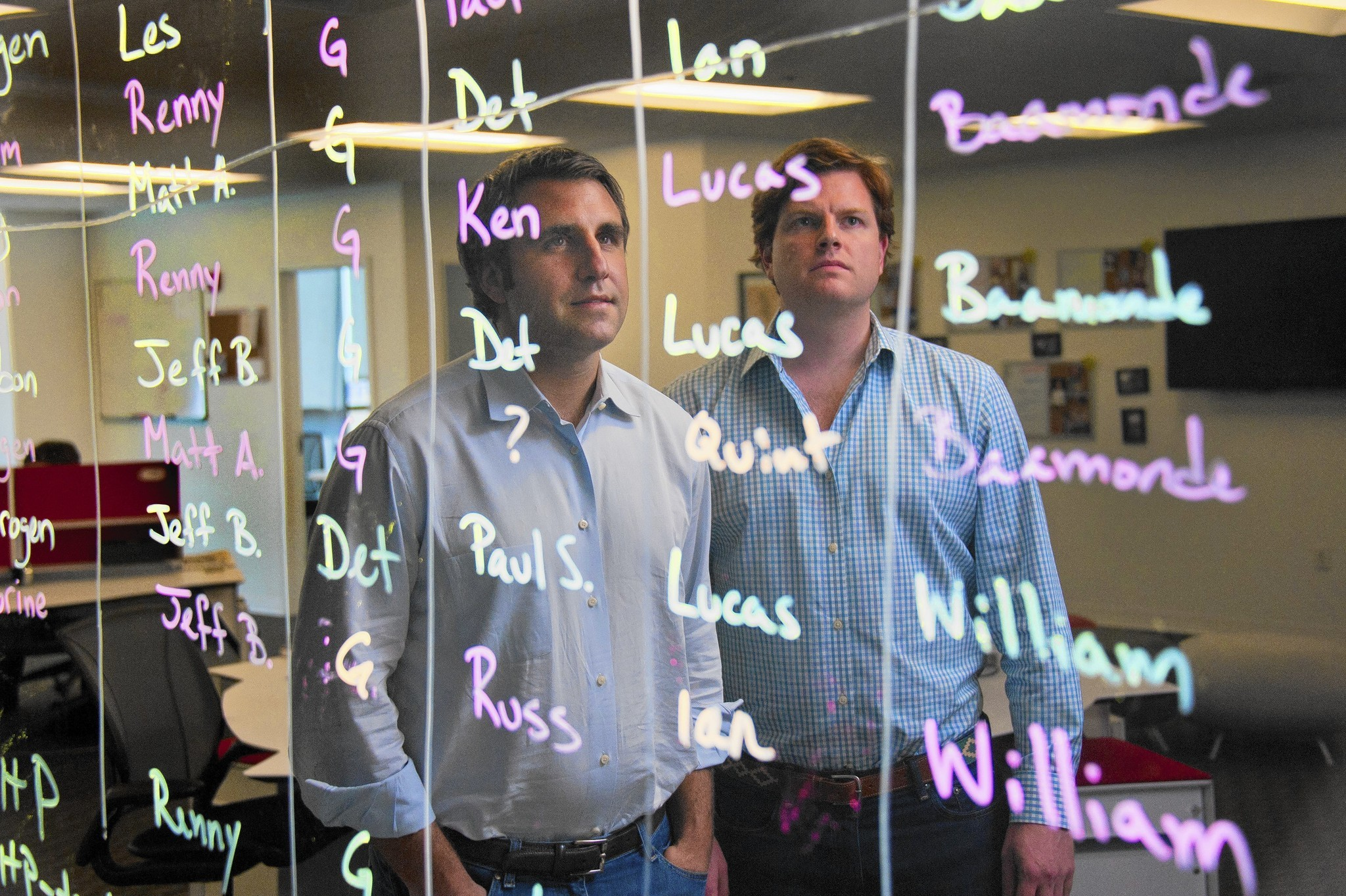 Co-founders Guy Filippelli (left) and Renny McPherson are reflected on a board with names of team members at RedOwl Tuesday, Jun 24, 2014.