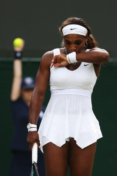 Serena Williams of the United States stands dejected during her Ladies' Singles third round match against Alize Cornet of France on day six of the Wimbledon Lawn Tennis Championships at the All England Lawn Tennis and Croquet Club at Wimbledon on June 28, 2014 in London, England.