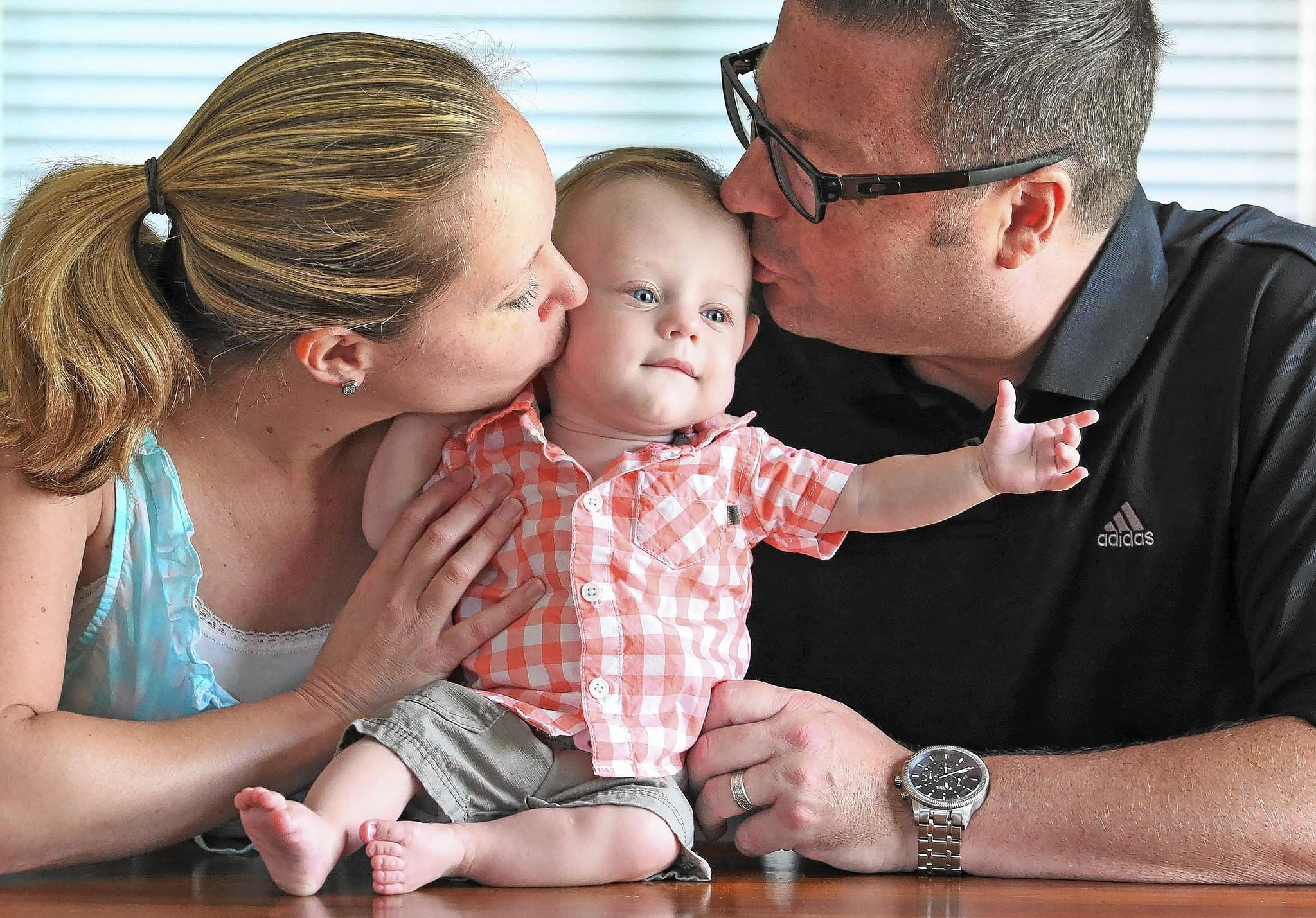 Holly and Eric Sorensen give a kiss to their 1-year-old son, Connor Sorensen.