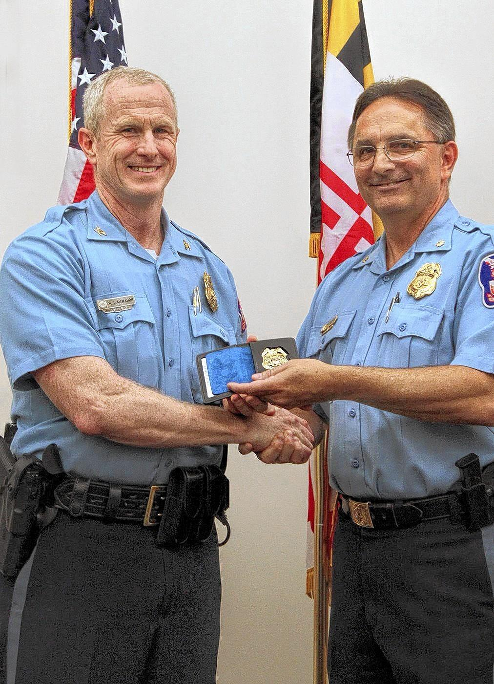 Police Chief William McMahon, left, was presented with a retirement badge after a 30-year career in law enforcement, including eight as the head of the department. Maj. Gary Gardner, right, who succeeds McMahon effective July 1, presented McMahon with the badge.