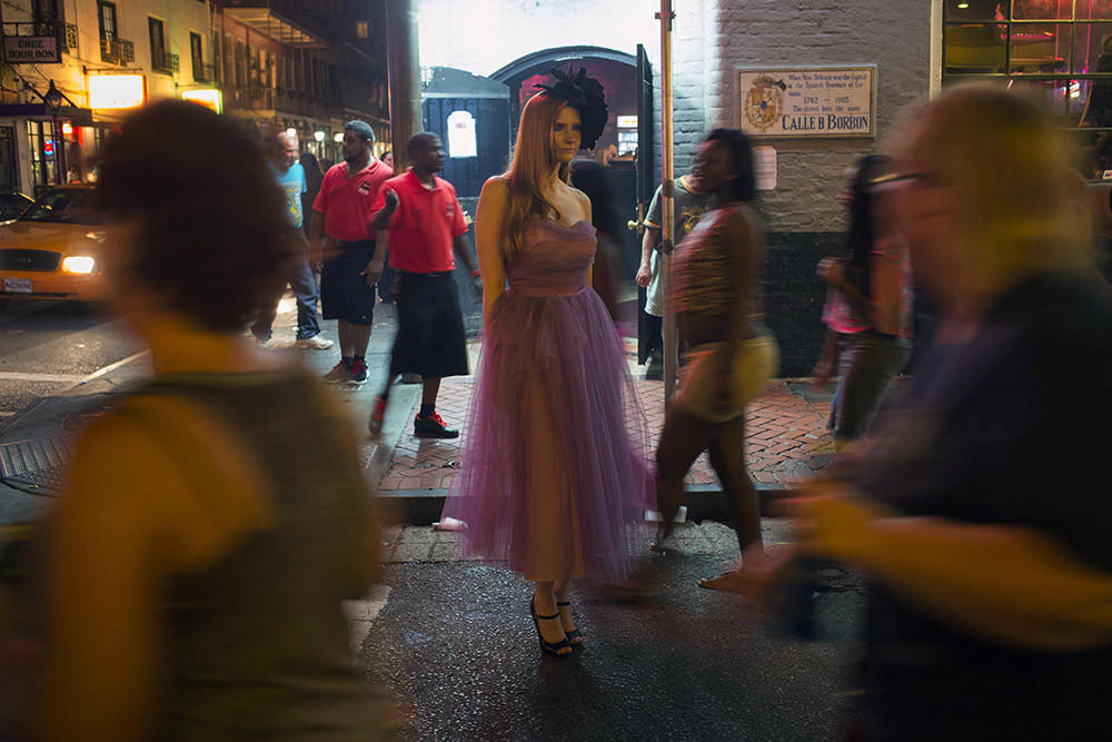 A model poses for photographs as revelers pass by on Bourbon Street in the French Quarter of New Orleans on June 6.