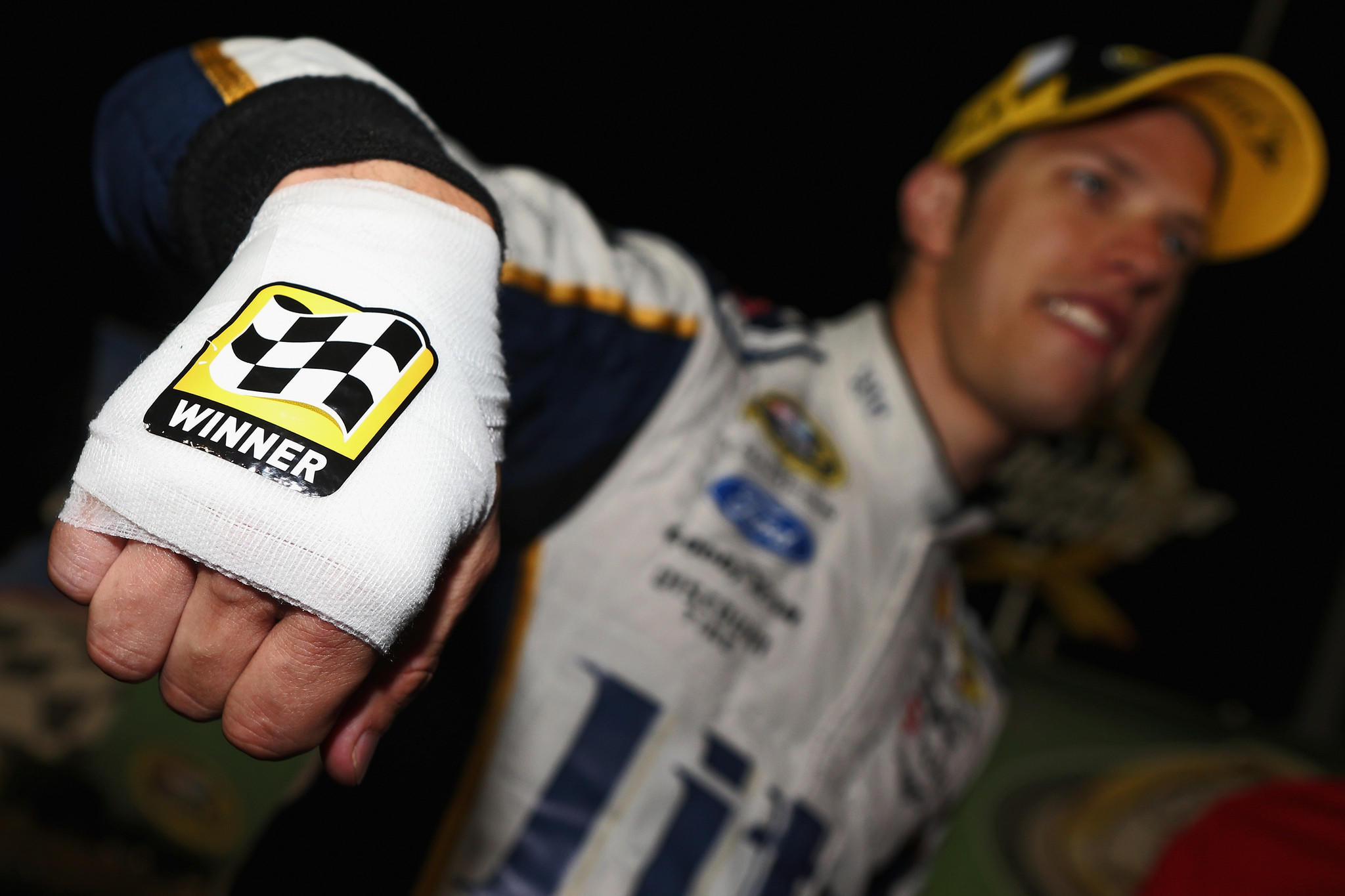 Brad Keselowski, driver of the #2 Miller Lite Ford, shows his bandaged hand after cutting himself while celebrating with champagne in Victory Lane after winning the NASCAR Sprint Cup Series Quaker State 400 presented by Advance Auto Parts at Kentucky Speedway.