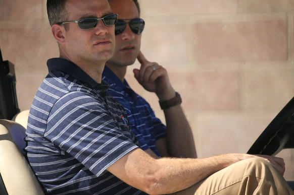 Theo Epstein and GM Jed Hoyer observe practice from a golf cart at the new practice facility and stadium in Mesa, Arizona.