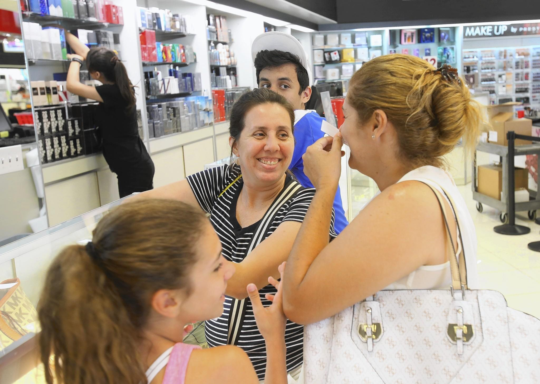 Fabiola Bordallo, center, tests scents at Perfumeland with her family from Rio de Janeiro.