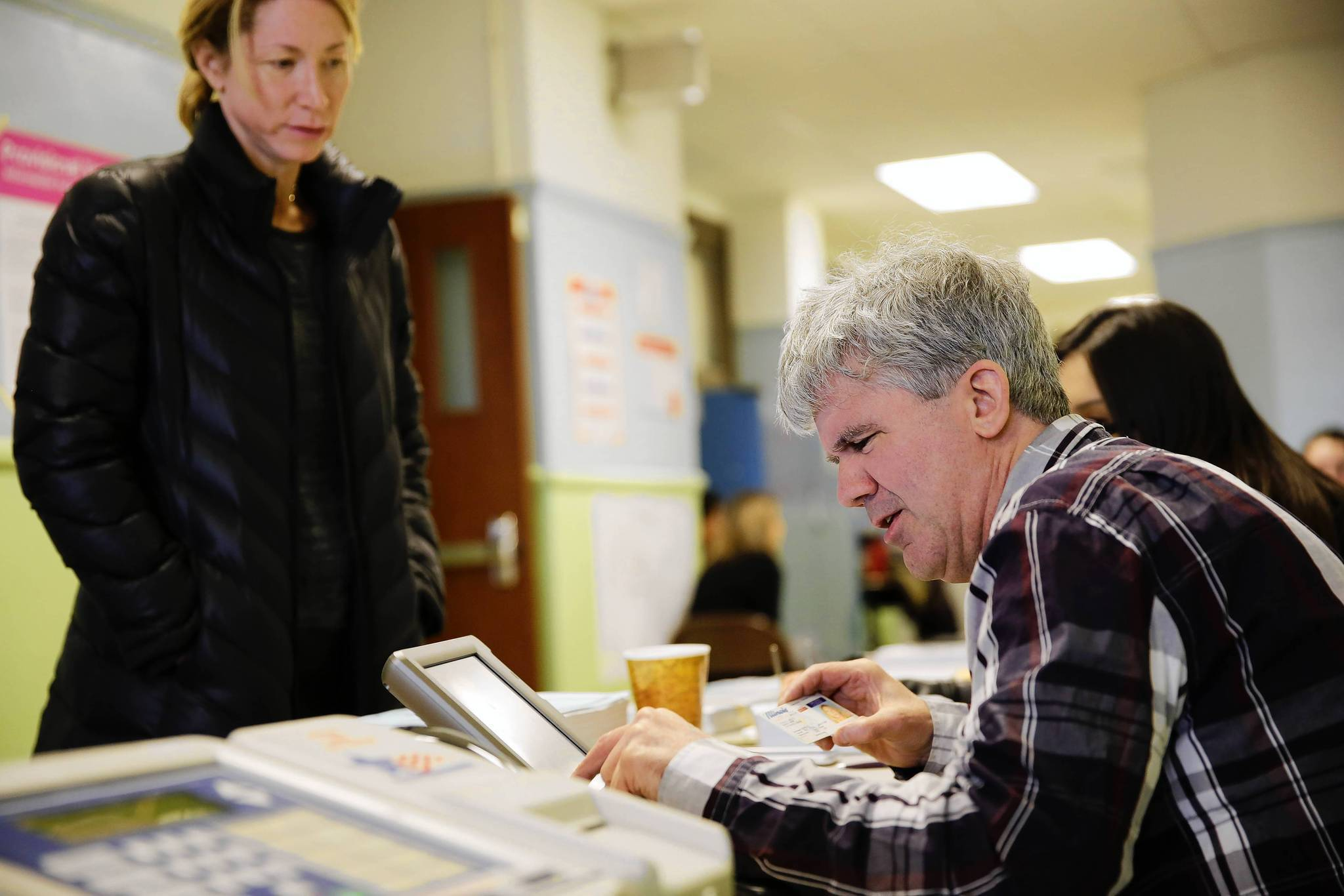 Election judge Daniel O'Donoghue looks over information from voter Stacy Kelly on primary election day in Chicago in March. This fall, voters will be able to register to vote on the same day they cast their ballots.