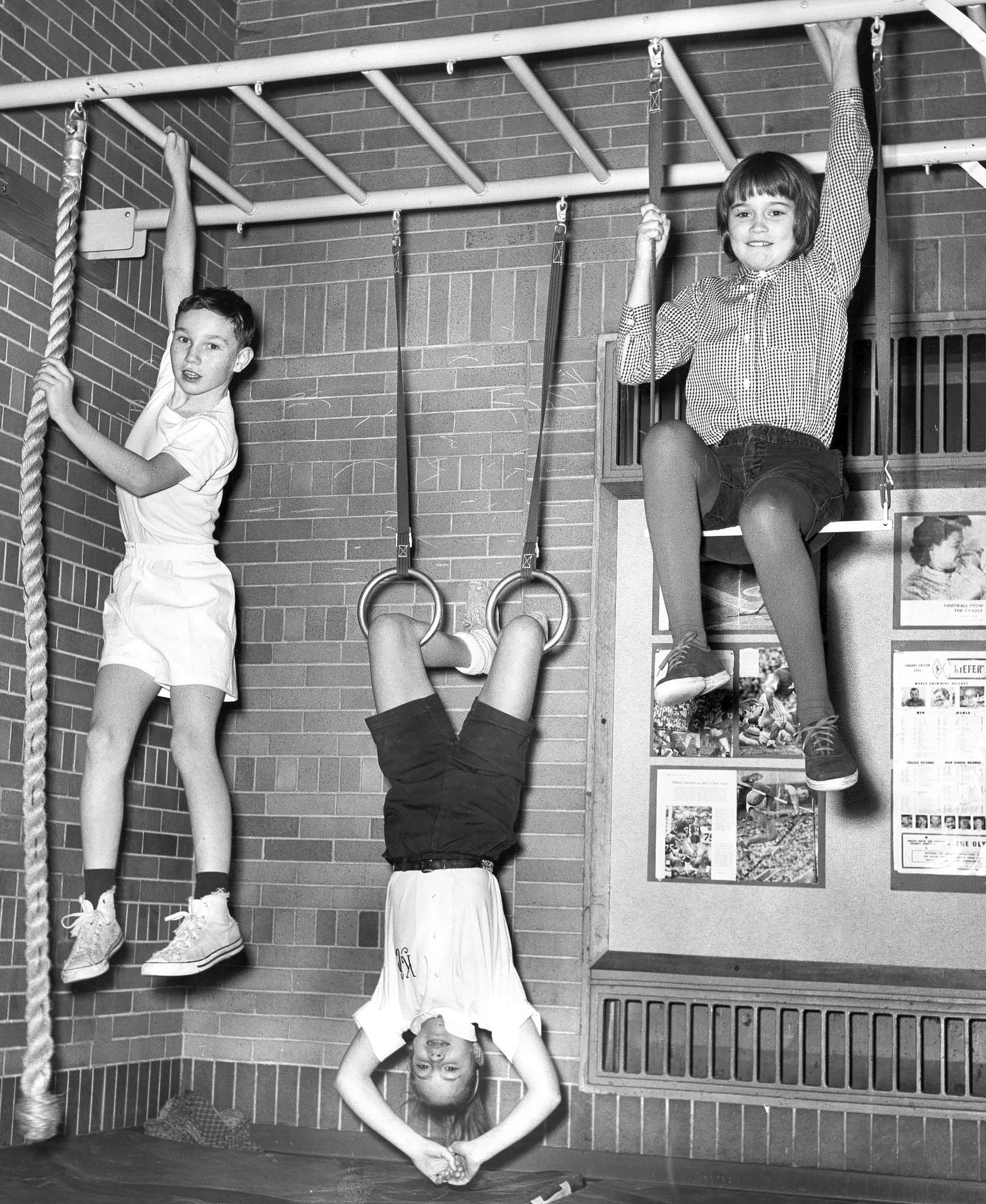 "Tom Hanley, 11, from left, Kathy Collins, 10, and Barabard Reynolds, 10, all fifth-graders at Washington Elementary, go through their daily gym routine in 1962. Kids in the 1960s listened to ""The Youth Fitness Song,"" written by Meredith Willson, while exercising at school as part of a fitness initiative by President John F. Kennedy. Apple now uses the song in its ads."