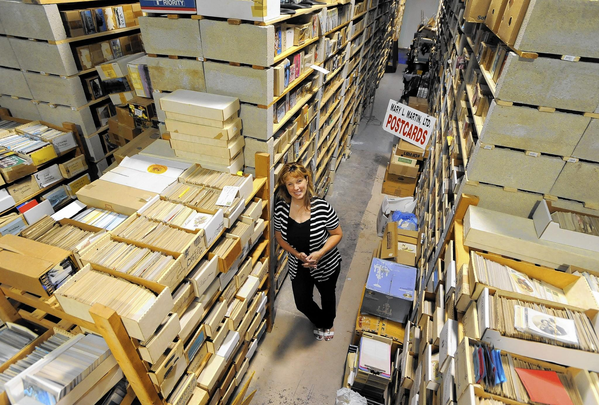 Mary Martin stands inside her warehouse of postcards in Perryville.