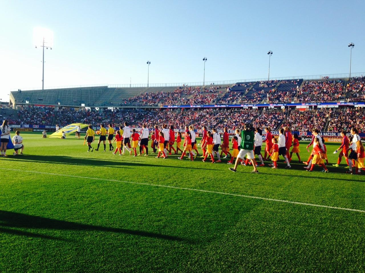 Players from the U.S. Women's National Soccer Team are escorted on to Rentscler Field by members of the Hartwell Soccer Club.